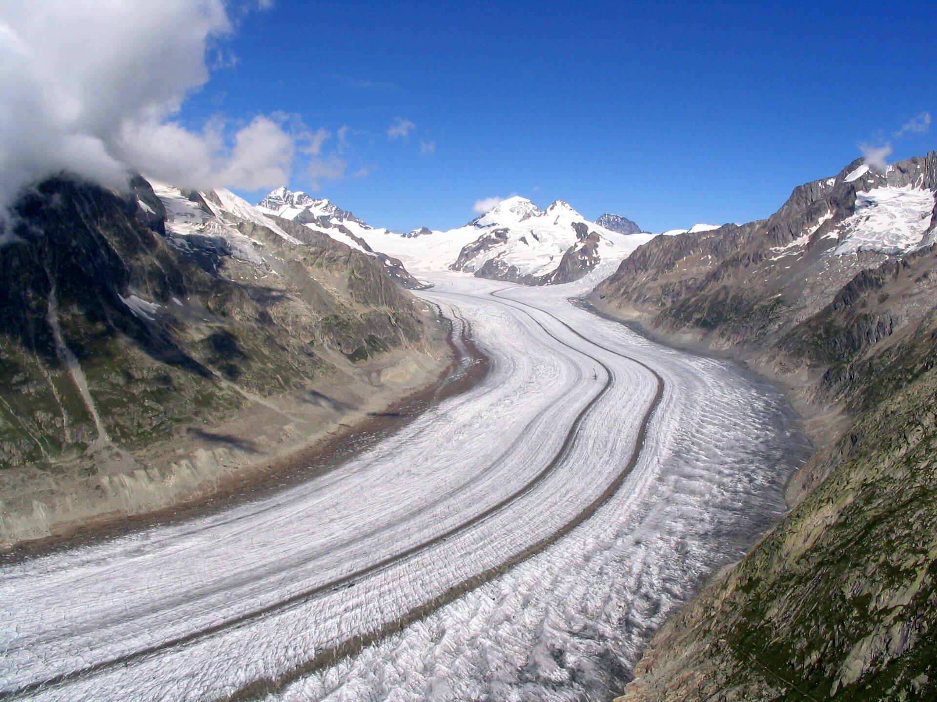 Zdjęcie przedstawia Alpy. Na pierwszym planie długi jęzor lodowca. Na prawo ilewo skaliste stoki gór. Na linii horyzontu szczyty gór pokryte śniegiem ilodem. Niebo błękitne.