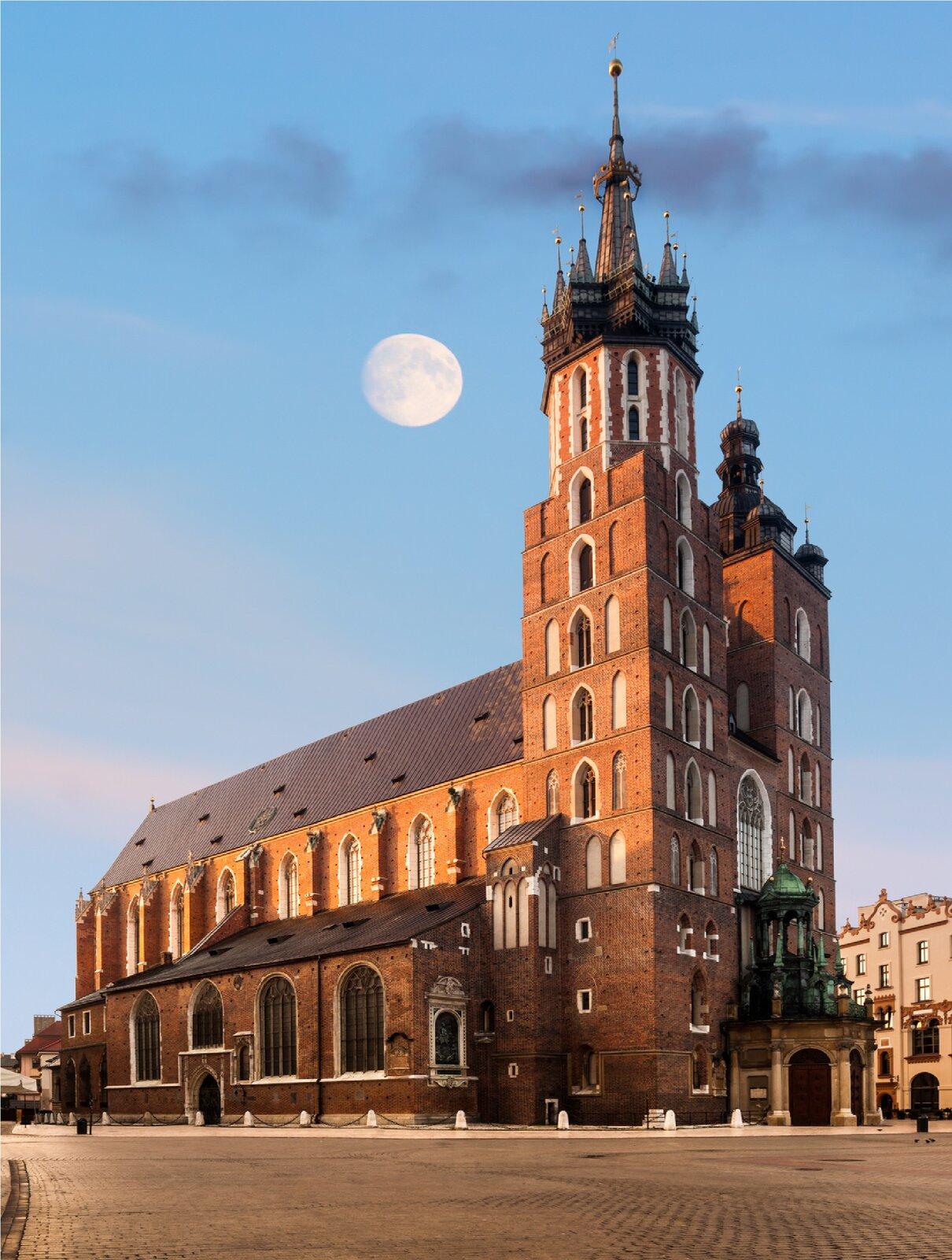 Ilustracja przedstawia Kościół Mariacki wKrakowie. Na zdjęciu ukazana jest budowla gotycka zczerwonej cegły zdwoma, nierównej wysokości wieżami we frontowej części. Wieża zlewej strony jest wyższa. Wieńczy ją gotycki hełm składający się zośmiobocznej, zaostrzonej iglicy, otoczonej ośmioma niższymi wieżyczkami. Niższa wieża po prawej jest prostsza wswej formie. Na froncie bazyliki znajduje się prowadząca do wnętrza barokowa kruchta zwieńczona ażurową wieżyczką. Liczne okna zakończone są ugóry charakterystycznym dla gotyku ostrym łukiem. Budowla ustawiona jest na krakowskim rynku. Nad nią, na tle nieba świeci duża tarcza księżyca.