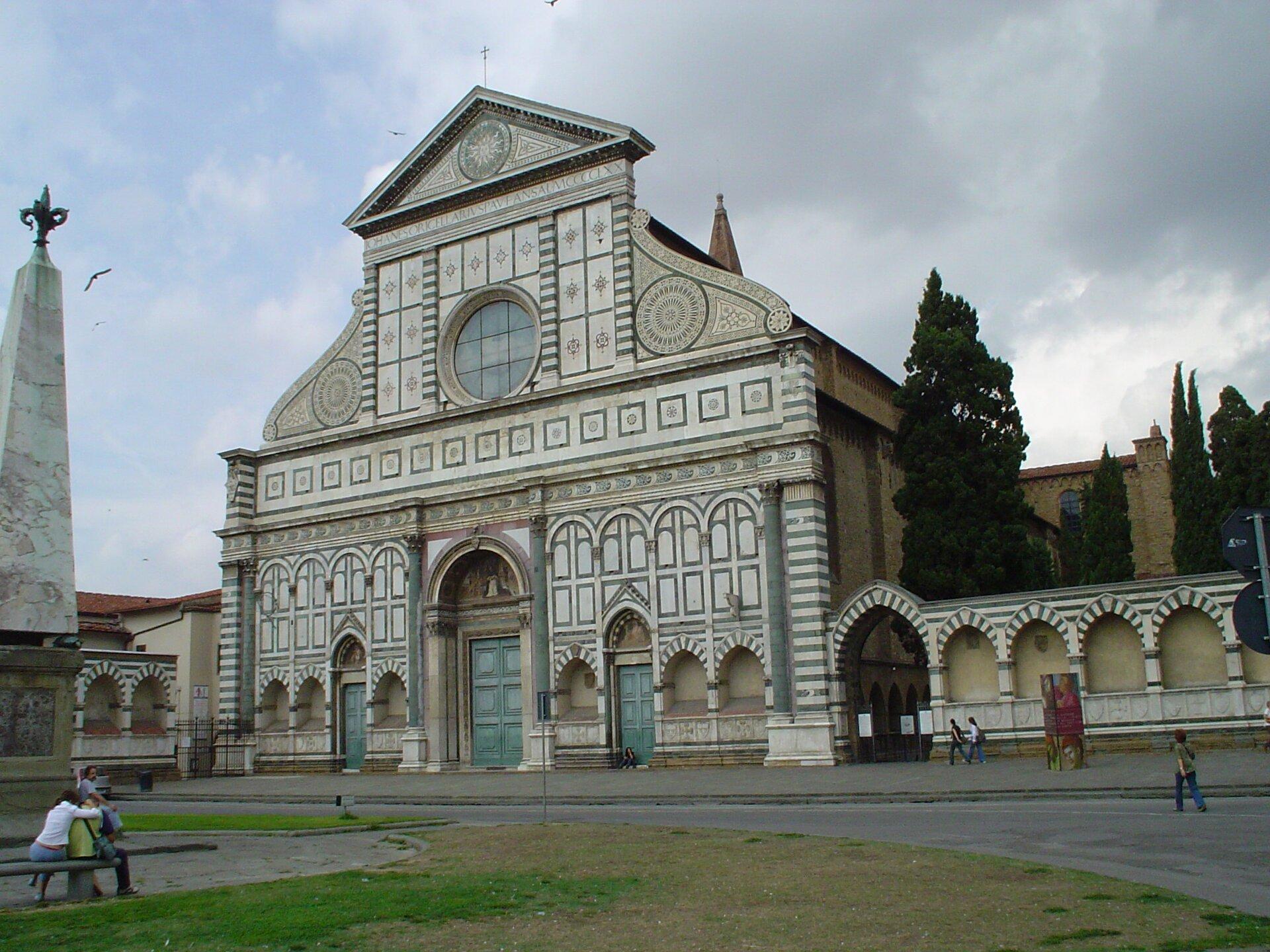 Fasada kościoła Santa Maria Novella we Florencji.Fasadaśredniowiecznego kościoła przyklasztornego dominikanów zaprojektowana została przez znanego teoretyka architektury renesansowej L.B. Albertiego iwykonana wlatach 1456-1470. Zwróć uwagę na połączenie elementów gotyckich wpostaci kilku zwieńczeń ostrołukowych zdominującymi łukami półkolistymi nawiązującymi do tradycji rzymskich łuków triumfalnych. Ważnym elementem było zastosowanie spływów wolutowych - wykończeń dachu wkształcie ślimacznicy stanowiących zamknięcie połaci dachowej między wyższą nawą główną aniższymi nawami bocznymi. Stanie się to stałym elementem późniejszych fasad renesansowych, aprzede wszystkim barokowych. Fasada kościoła Santa Maria Novella we Florencji.Fasadaśredniowiecznego kościoła przyklasztornego dominikanów zaprojektowana została przez znanego teoretyka architektury renesansowej L.B. Albertiego iwykonana wlatach 1456-1470. Zwróć uwagę na połączenie elementów gotyckich wpostaci kilku zwieńczeń ostrołukowych zdominującymi łukami półkolistymi nawiązującymi do tradycji rzymskich łuków triumfalnych. Ważnym elementem było zastosowanie spływów wolutowych - wykończeń dachu wkształcie ślimacznicy stanowiących zamknięcie połaci dachowej między wyższą nawą główną aniższymi nawami bocznymi. Stanie się to stałym elementem późniejszych fasad renesansowych, aprzede wszystkim barokowych. Źródło: Maksim, Wikimedia Commons, licencja: CC BY-SA 3.0.