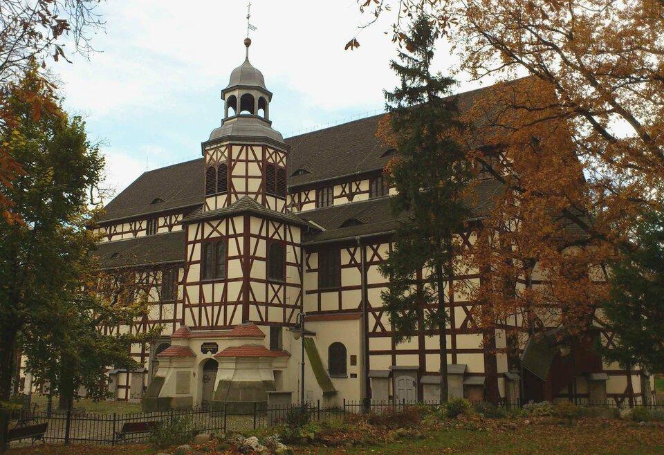 Na zdjęciu drewniany kościół okonstrukcji szachulcowej – ściana szkieletowa drewniana, (ciemne belki ułożone wkratkę iskos), wypełnienie stanowi glina otynkowana na kolor piaskowy. Dach skośny brązowy, jedna wieża.