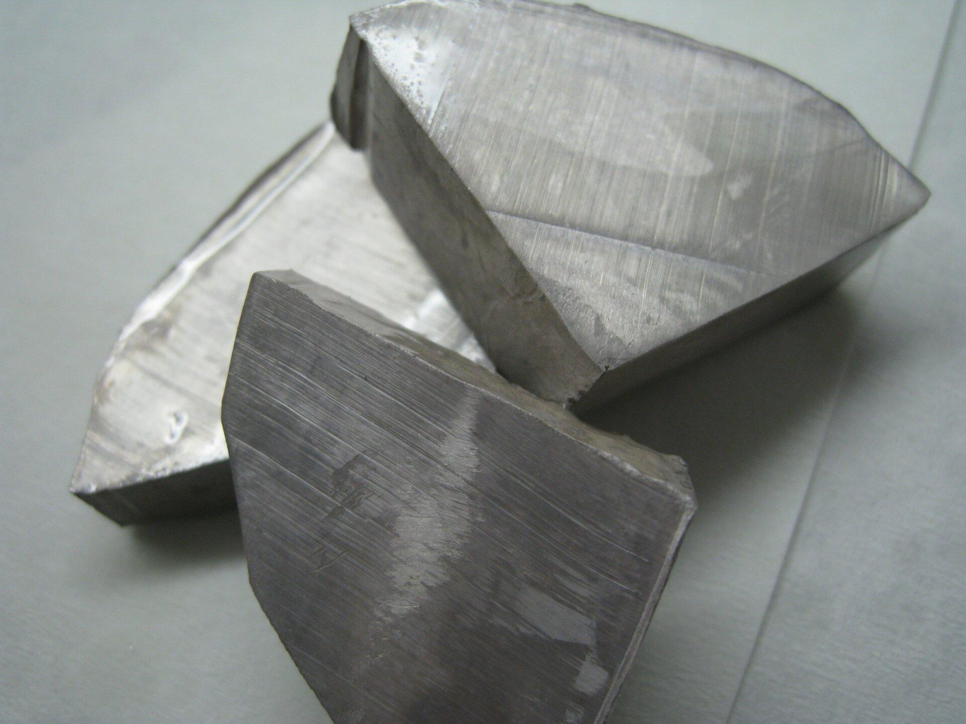 Zdjęcie przedstawia trzy kawałki metalicznego sodu leżące na białej powierzchni. Każdy zkawałków ma co najmniej trzy ścianki równe zwidocznymi śladami po cięciu. Pozostałe krawędzie nieregularne. Metal jest srebrny zwyraźnymi plamami szarego nalotu wmiejscach, gdzie zaczął reagować zpowietrzem.