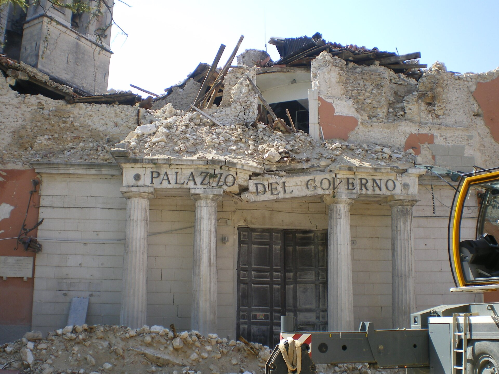 Na zdjęciu zawalony budynek, ocalał parter, przed budynkiem zwały gruzu.