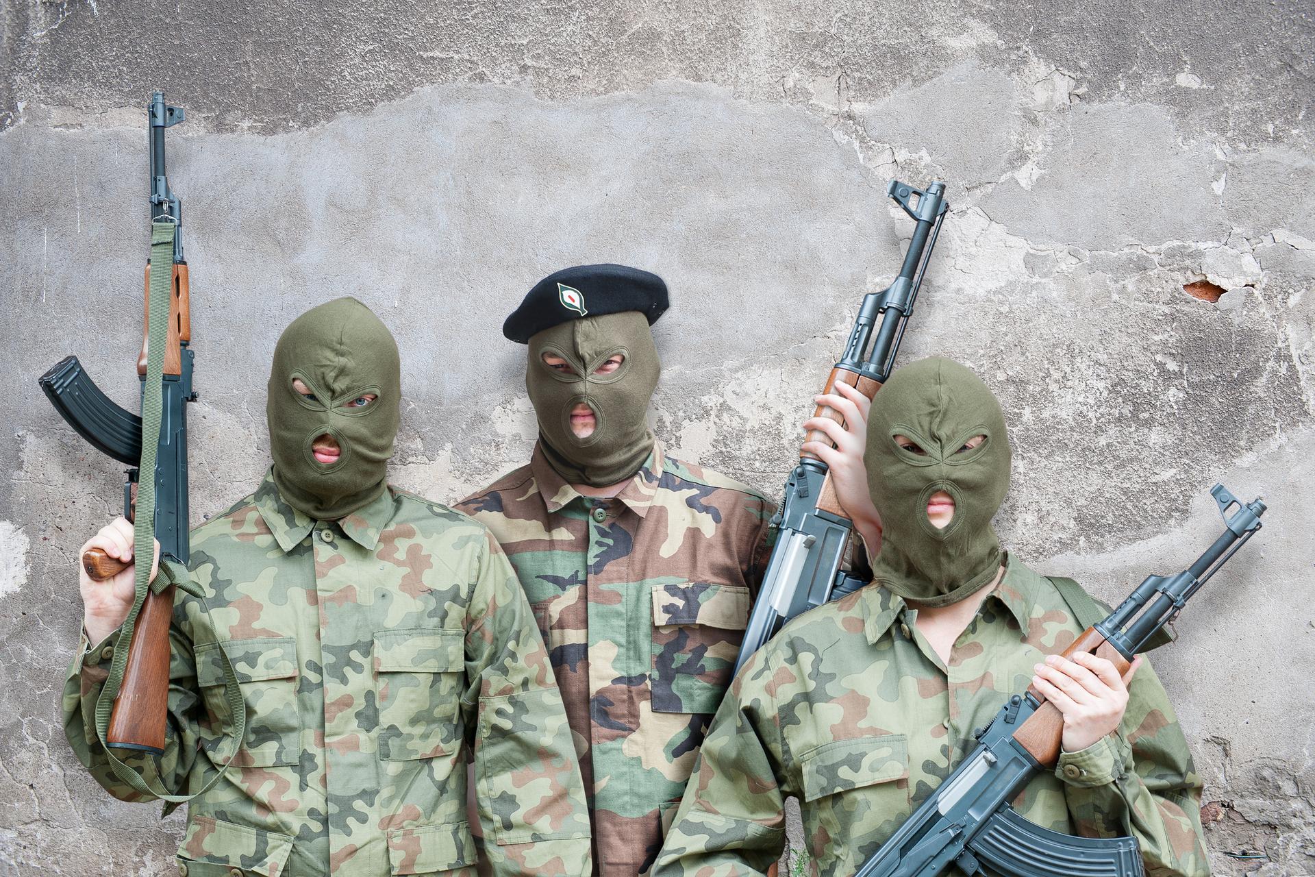 Zdjęcie przedstawia trzech żołnierzy Irlandzkiej Armii Republikańskiej. Żołnierze stoją przodem do obserwatora zdjęcia. Ubrani wwojskowe mundury, na głowach zielone kominiarki. Każdy trzyma karabin. Lufy karabinów skierowane do góry. Żołnierz stojący ztyłu, pomiędzy dwoma zprzodu, ma na głowie czarny beret.