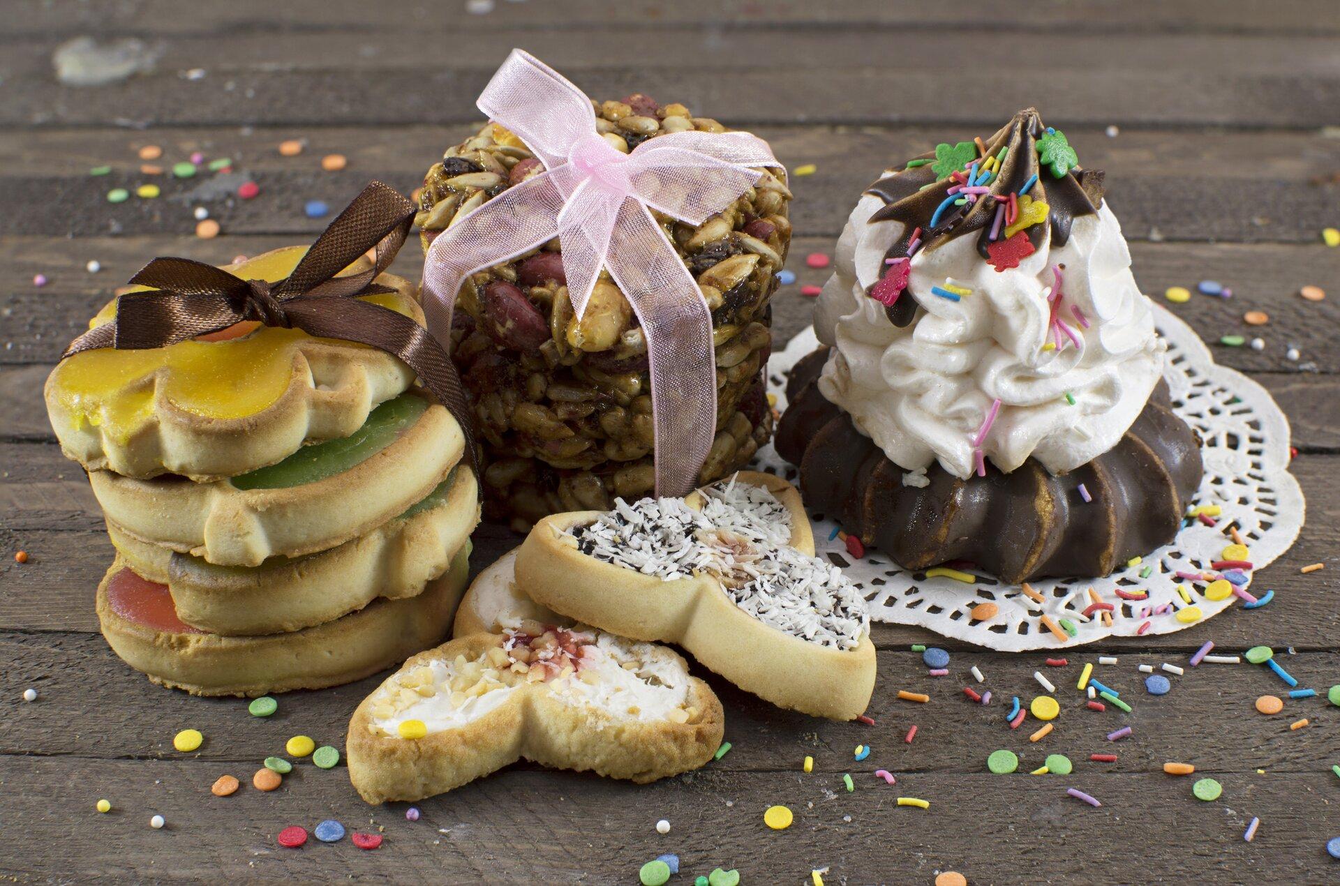 Ilustracja  przedstawia zdjęcie ciasteczek. Na drewnianym blacie znajdują się różnego rodzaju ciastka. Niektóre są lukrowane, inne posypane wiórkami kokosowymi. Dwa rodzaje znich ookrągłym kształcie ułożono wstosiki iprzewiązano różową ibrązową wstążką. Po prawej stronie, na białej, okrągłej serwetce leży oblane czekoladą ciastko przyozdobione bitą śmietaną.