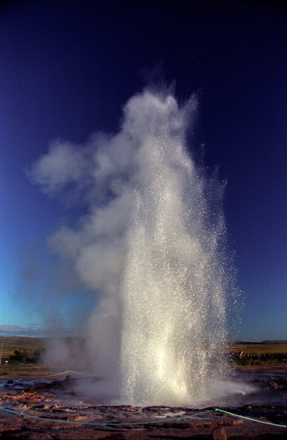 Fotografia ukazuje fontannę wody tryskającej zgejzeru.