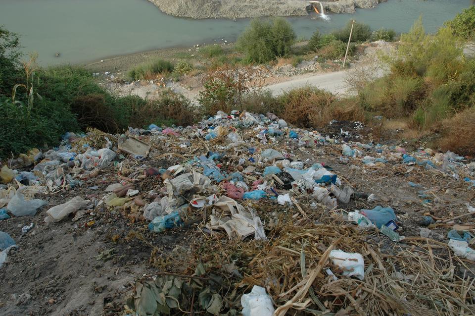Fotografia prezentuje dzikie wysypisko. Widoczne porozrzucane kolorowe śmieci na górce. Poniżej górki widoczna droga oraz woda.