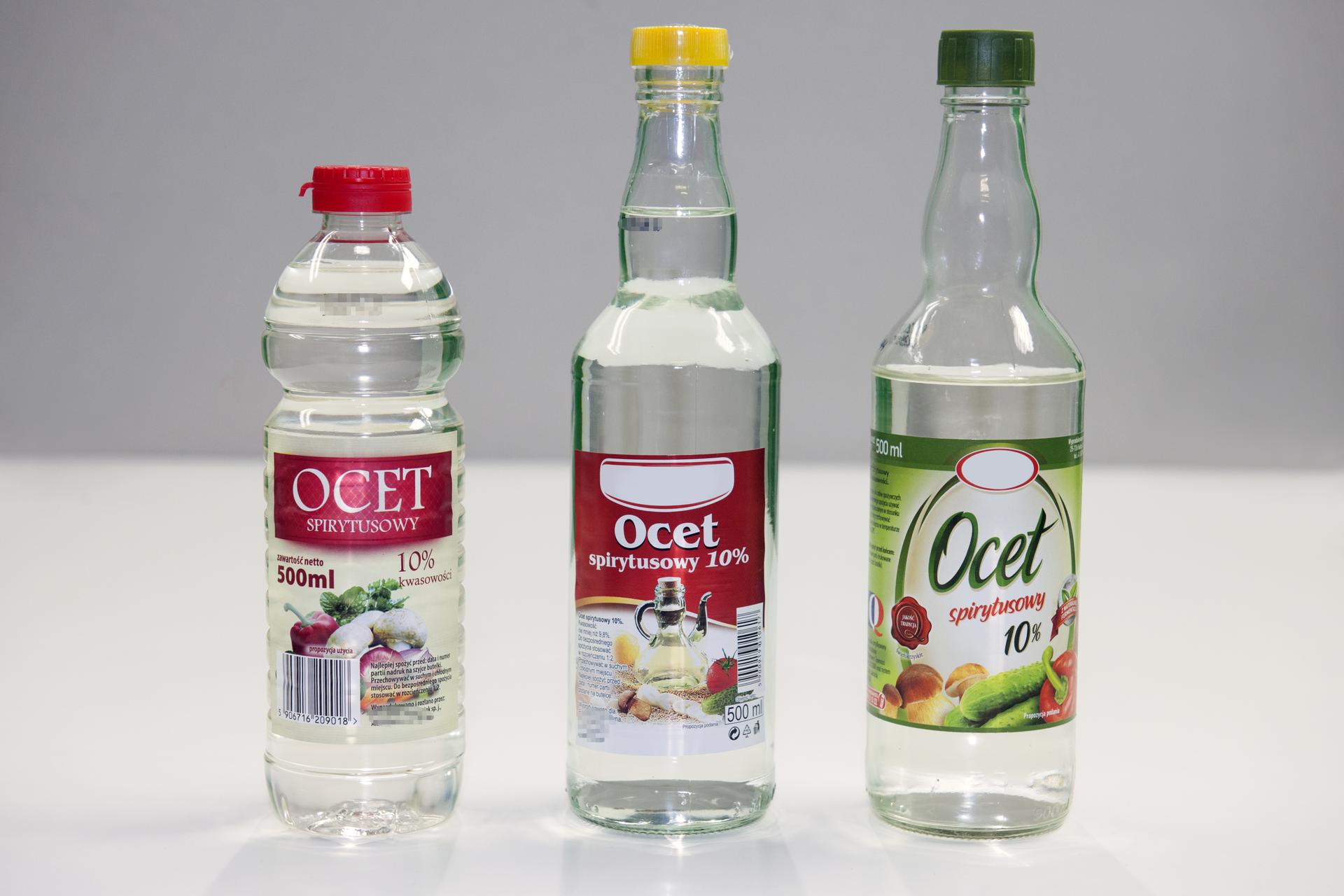 Zdjęcie przedstawia trzy stojące obok siebie na płaskim, białym podłożu butelki zoctem różnych producentów. Widoczne są nalepki, które wskazują, że wkażdym przypadku ocet ma jednakowe stężenie. Wynosi ono dziesięć procent.