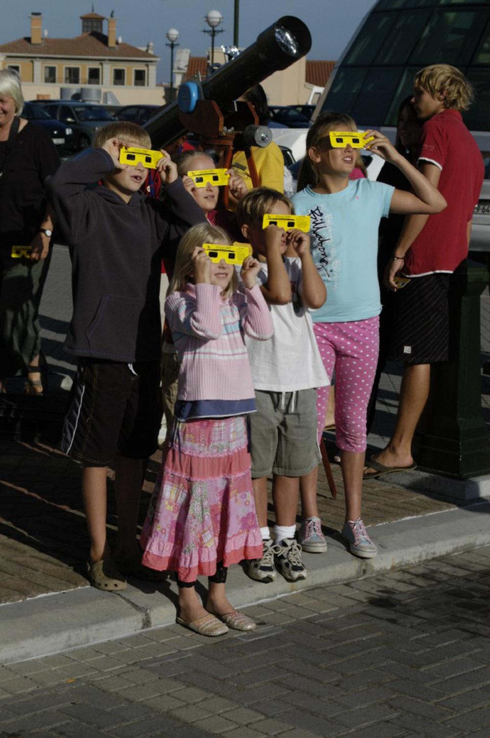 Fotografia przedstawiająca grupę dzieci wróżnym wieku oglądających zaćmienie Słońca, przez specjalne okulary wżółtych oprawach. Za nimi widoczna luneta skierowana wniebo.