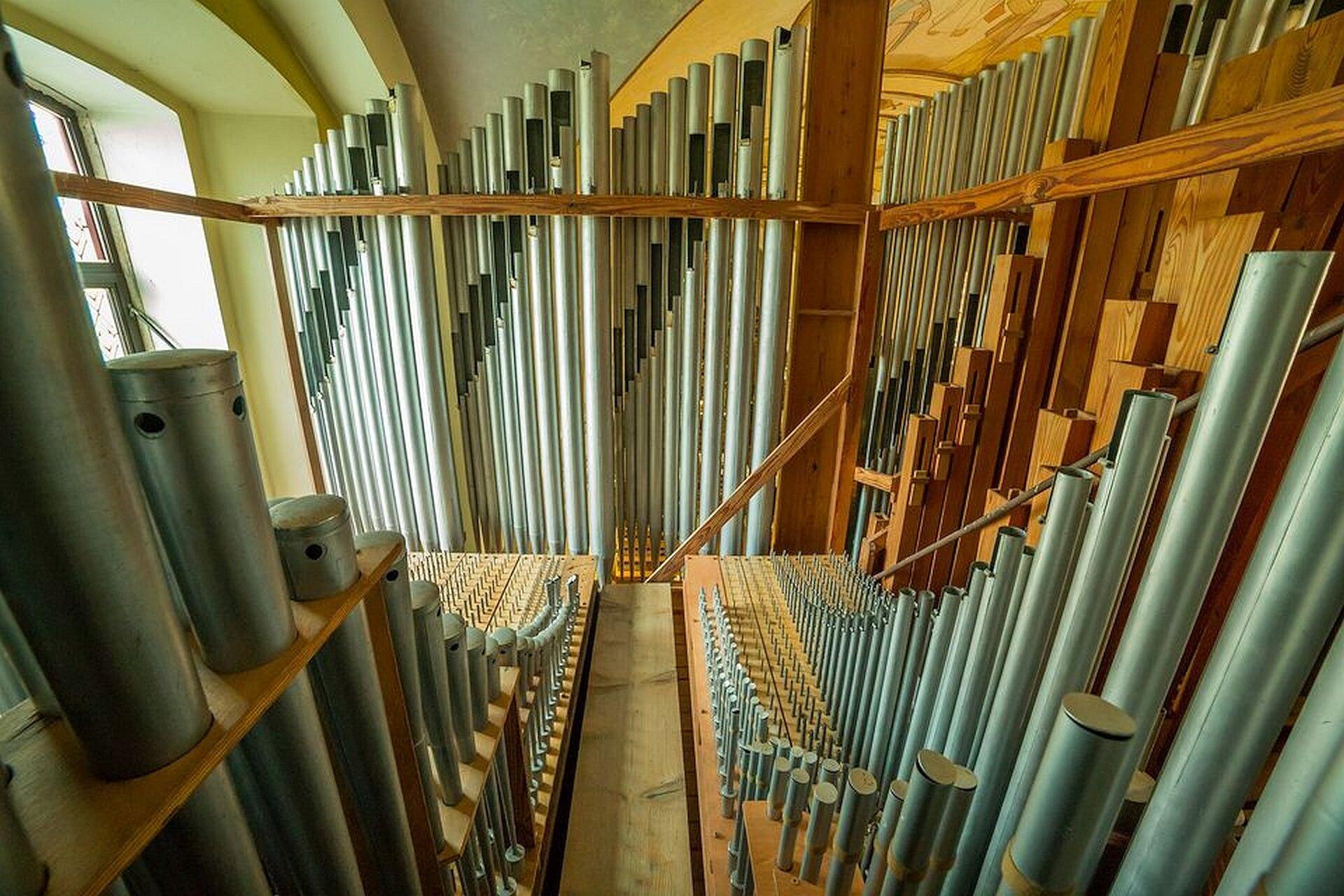 Zdjęcie przedstawiające fragment szafy organowej, czyli miejsca gdzie ustawione są piszczałki. Na zdjęciu bardzo duża ilość piszczałek metalowych idrewnianych ustawionych wrzędach od największych do najmniejszych.