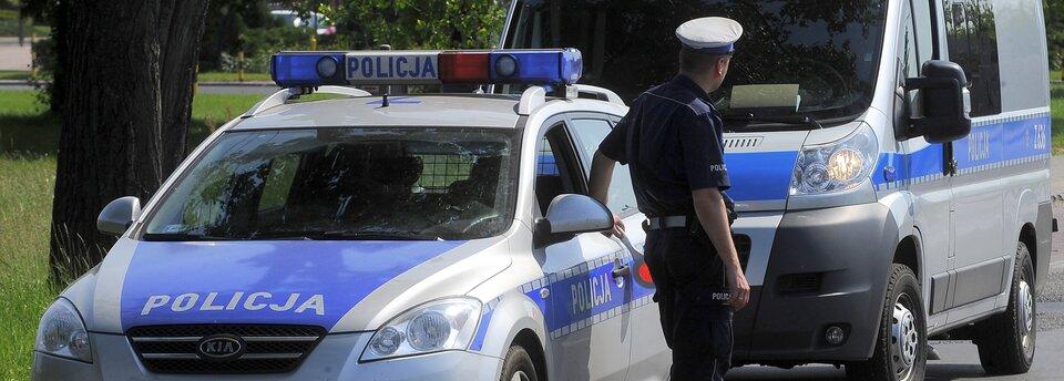 Kolorowe zdjęcia przedstawia dwa wozy policyjne zwrócone przodem do obserwatora. Tyłem do obserwatora, przy pierwszym wozie stoi policjant, ubrany wmundur zkrótkim rękawem. Policjant patrzy wstronę nadjeżdżających samochodów.