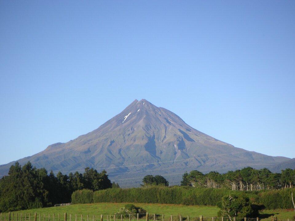 Na zdjęciu góra wkolorze szarym, okształcie stożka, na szczycie leży śnieg. Nie jest porośnięta roślinnością. Na pierwszym planie ogrodzona łąka, krzewy idrzewa.