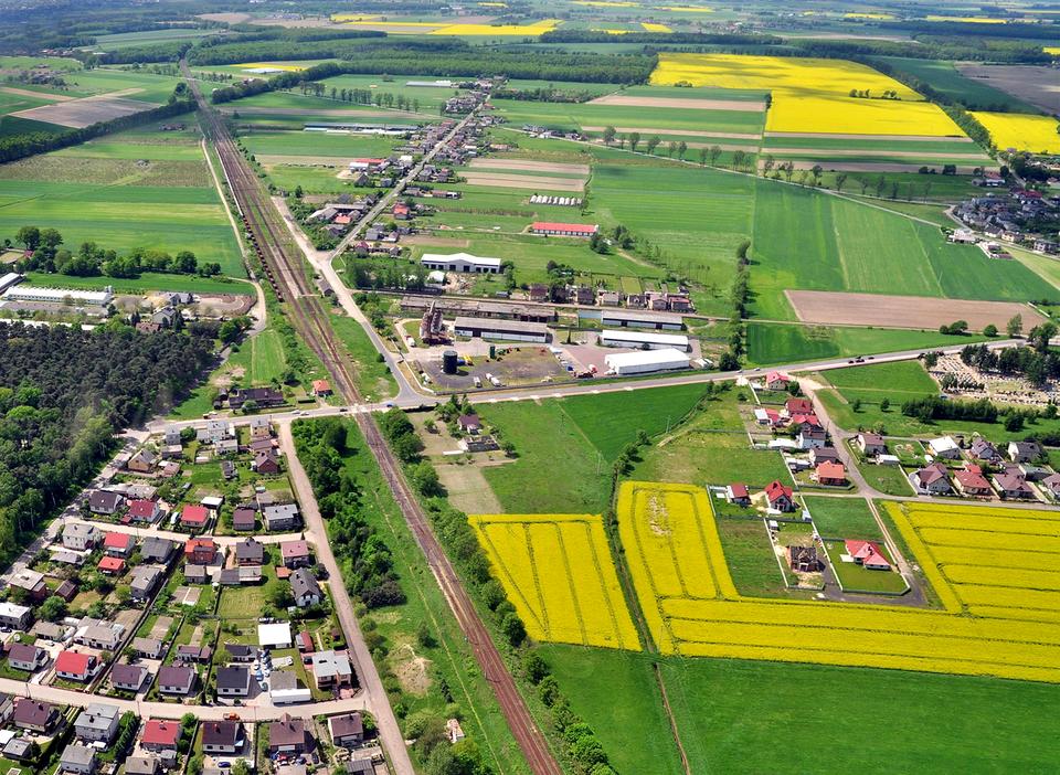 Trzecie zdjęcie przedstawia tereny nizinne Wielkopolski, widoczne liczne pola, łąki, zabudowania idrogi.