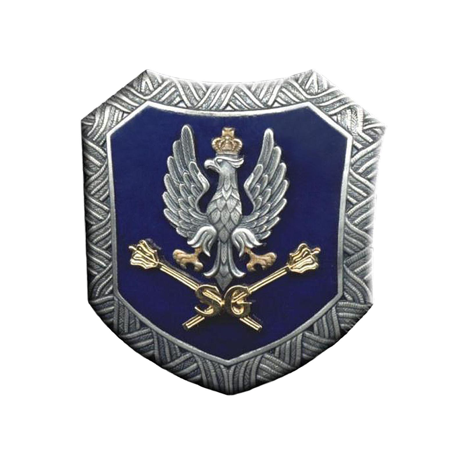 Ilustracja przedstawia logo Sztabu Generalnego Wojska Polskiego stylizowany na godło orła polskiego. Szary orzeł ze skrzydłami wzniesionymi ku górze. Głowa skierowana wlewo. Na głowie złota korona. Na szczycie korony krzyż. Szpony orła wkolorze złotym. Poniżej orła dwa skrzyżowane złote berła. Orzeł iberła na granatowym tle. Całość otacza metalowa ramka wkształcie trapezu.