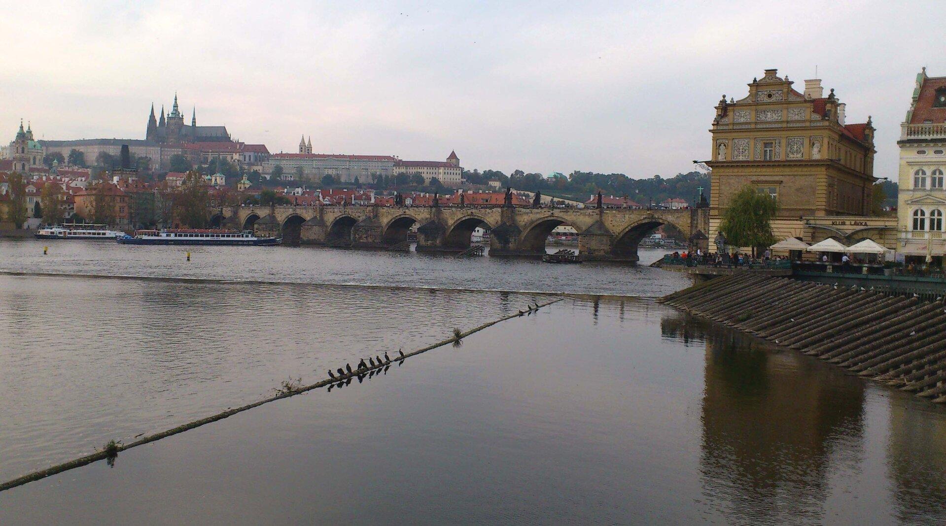 Na zdjęciu na pierwszym planie rzeka, dalej murowany most, woddali na wzgórzu zabytkowe budynki, kryte czerwonymi dachami, wysokie wieże.