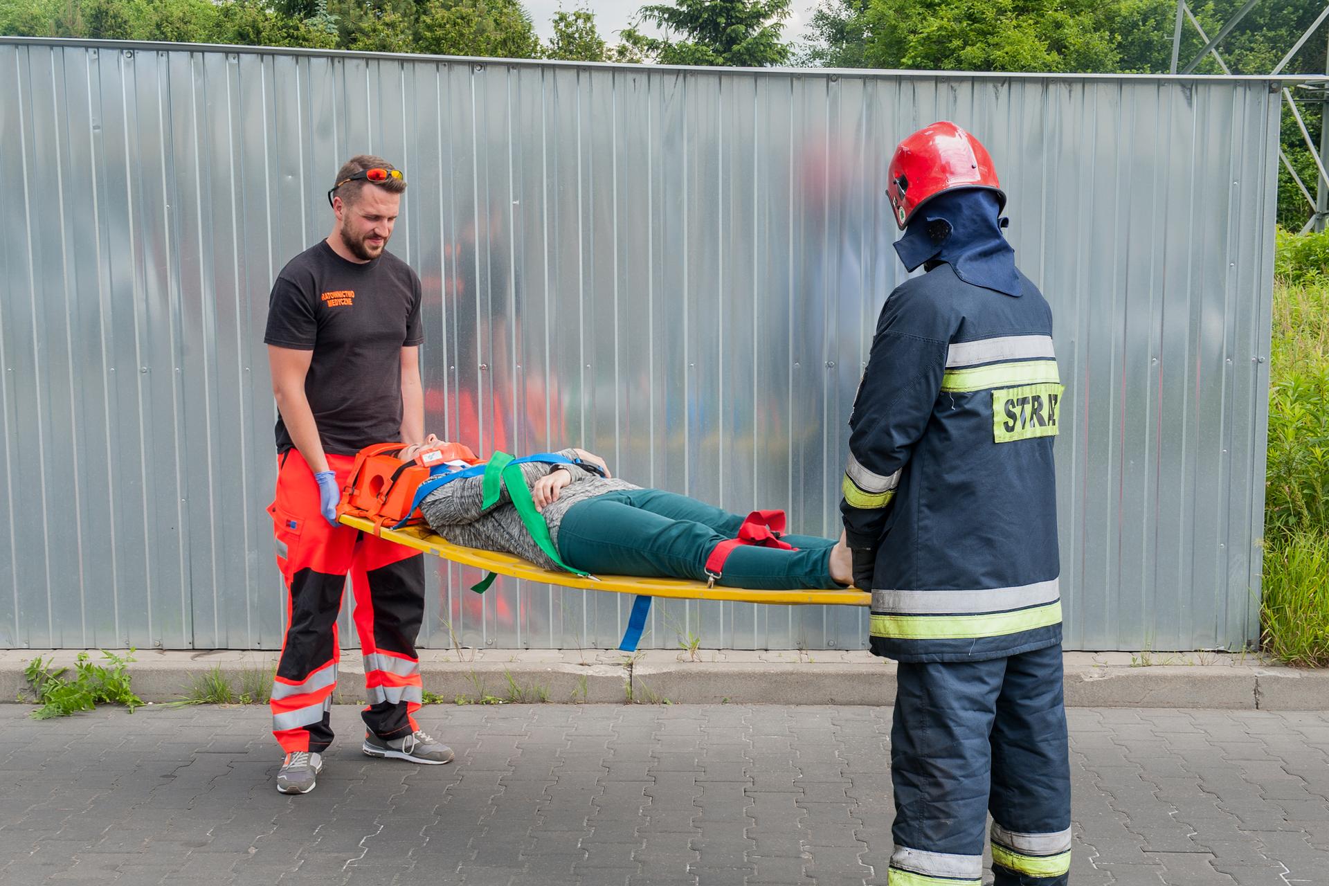 Kolorowe zdjęcie przedstawia dwóch mężczyzn niosących na noszach osobę poszkodowaną. Po lewej stronie ratownik medyczny. Ubrany na czarno. Wzdłuż nogawek spodni pomarańczowe iszare pasy odblaskowe. Po prawej strażak ubrany wmundur ratowniczy. Na głowie czerwony kask. Na plecach odblaskowy napis Strażak. Osoba poszkodowana ma unieruchomioną głowę wspecjalnym kołnierzu. Osoba jest przypięta pasami do noszy.