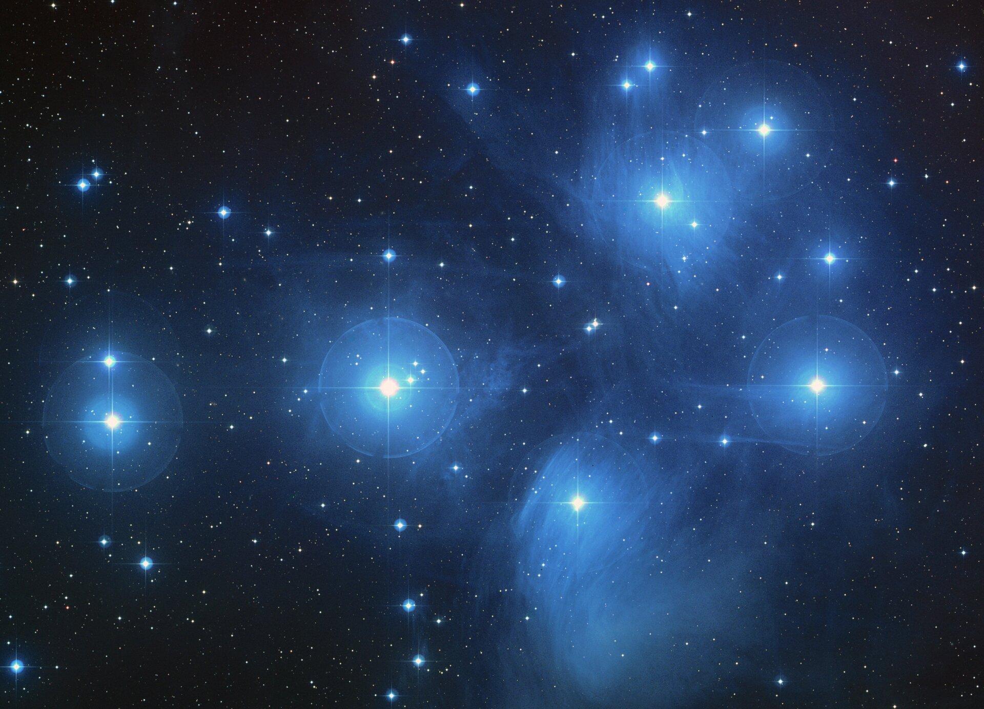 Grafika przedstawia gromadę gwiazd Plejady wGwiazdozbiorze Byka. Tło czarne. Na grafice widoczne mnóstwo jasnoniebieskich punktów różnej wielkości. Kilka największych wydają się być otoczone niebieską otoczką, łuną.
