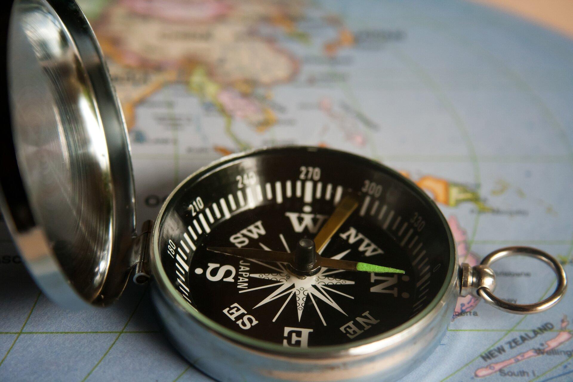 Fotografia prezentuje kompas turystyczny umieszczony na mapie świata. Kompas składa się zokrągłego przezroczystego pudełka, na dnie którego znajduje się tarcza znarysowanymi kierunkami świata oraz podziałka wstopniach. Nad tarczą zawieszona jest igła magnetyczna wskazująca kierunek północ -południe.