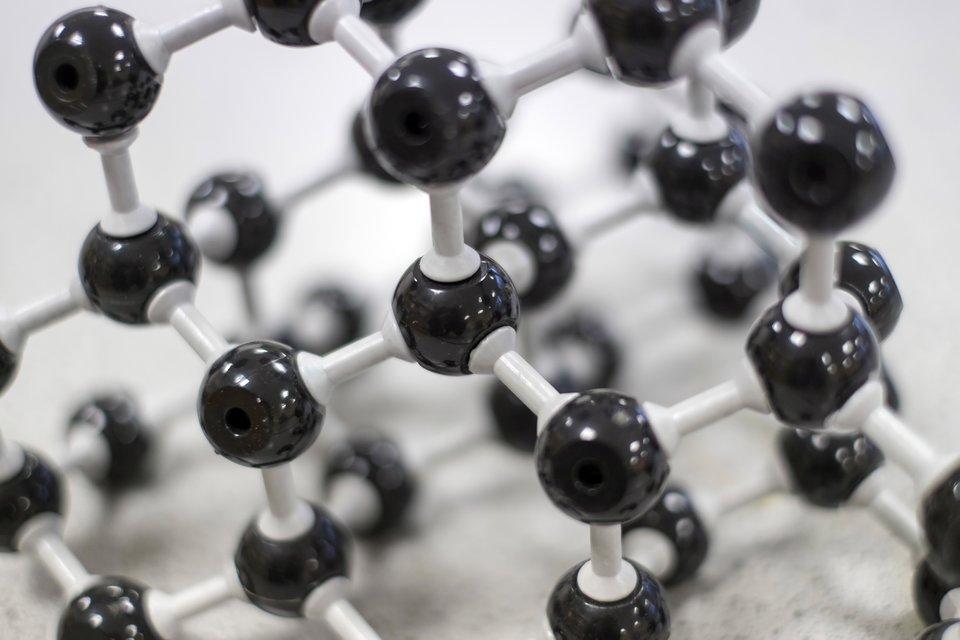 Fotografia przedstawia model drobinowy. Czarne elementy wkształcie kulek połączone są ze sobą wzajemnie szarymi, podłużnymi elementami. Wszystko wokół nas zbudowane jest zdrobin.