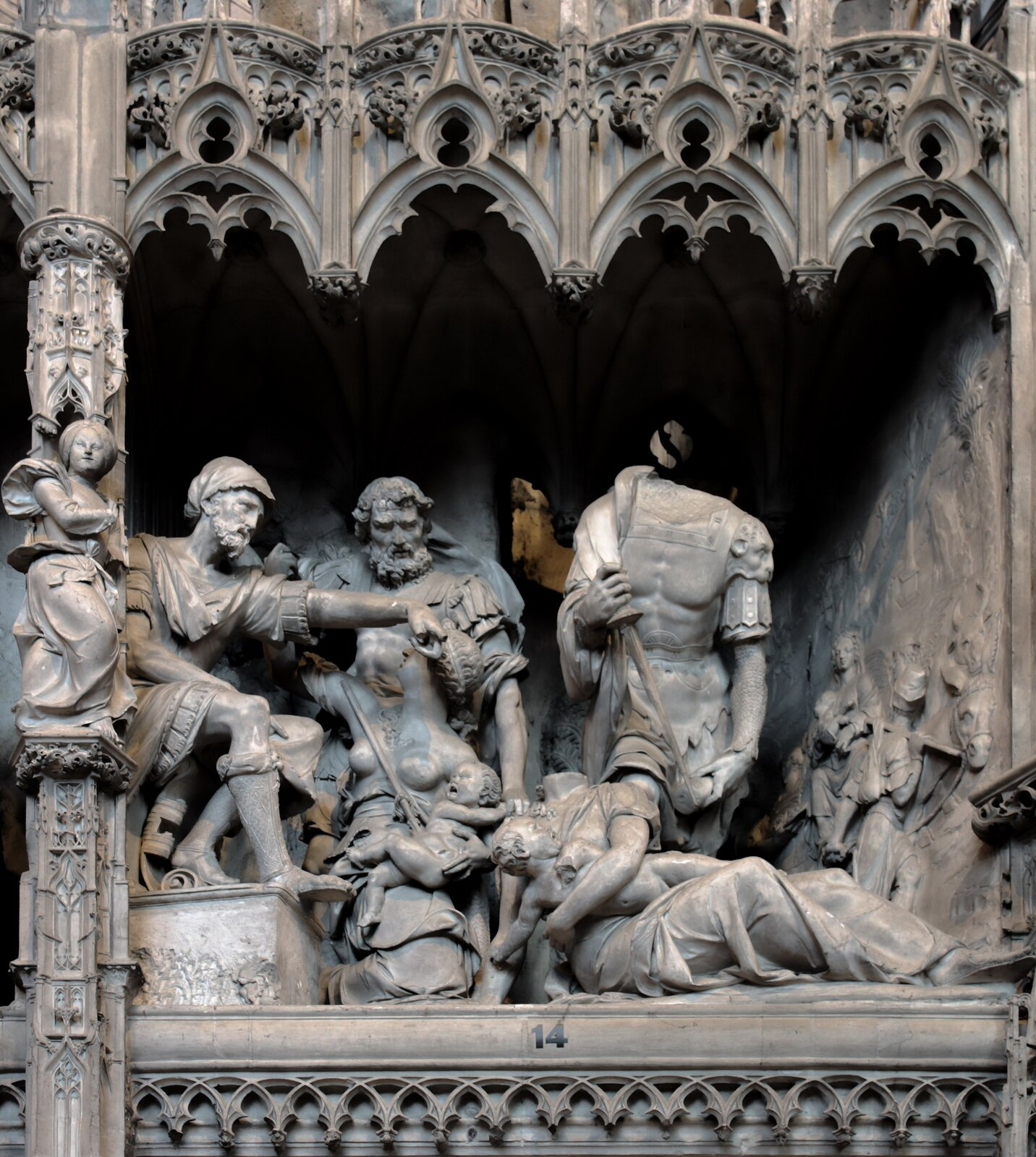 Ilustracja przedstawia wypukłorzeźby zgotyckiej katedry pod wezwaniem Najświętszej Marii Panny (Notre-Dame) wChartres we Francji. Na fotografii można zobaczyć wyrzeźbioną scenę, wktórej widoczni są ludzie zwysokiego rodu oraz leżące pod nimi kobiety zdziećmi na rękach.