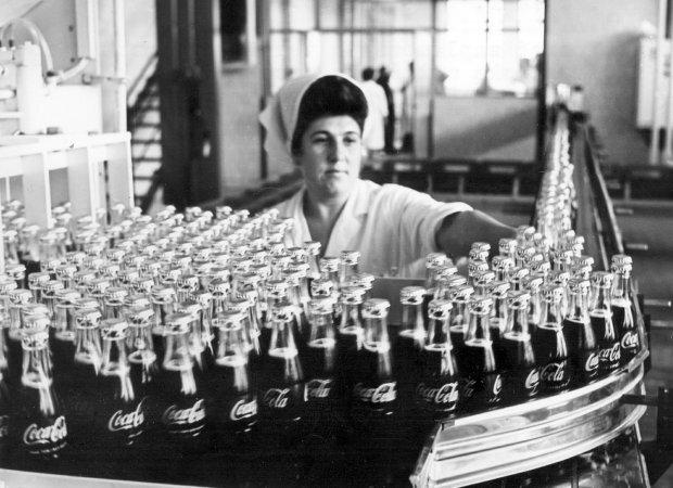 Fotografia czarno-biała przedstawiająca linię produkcyjną coca-coli wPolsce. Pracownica układa butelki napełnione napojem na taśmie.