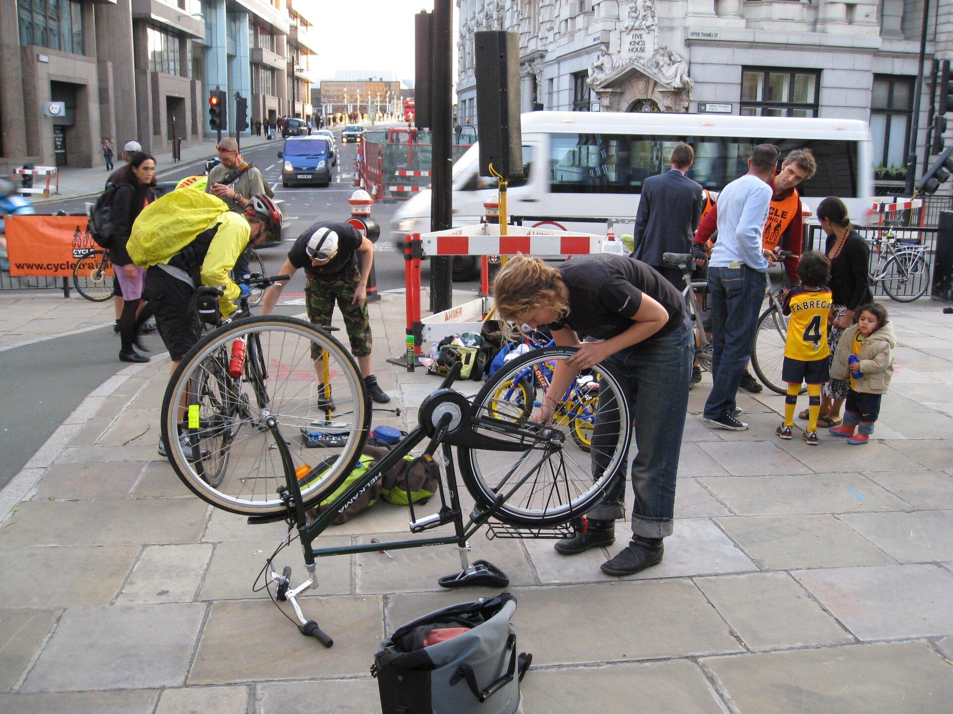 Zdjęcie przedstawia scenę zulicznym punktem obsługi rowerów, zorganizowanym przy okazji jakiegoś święta lub wyścigu. Na pierwszym planie młoda kobieta robi coś przy łańcuchu itylnym kole roweru stojącego do góry nogami. Wtle odbywają się przeglądy dwóch innych maszyn.