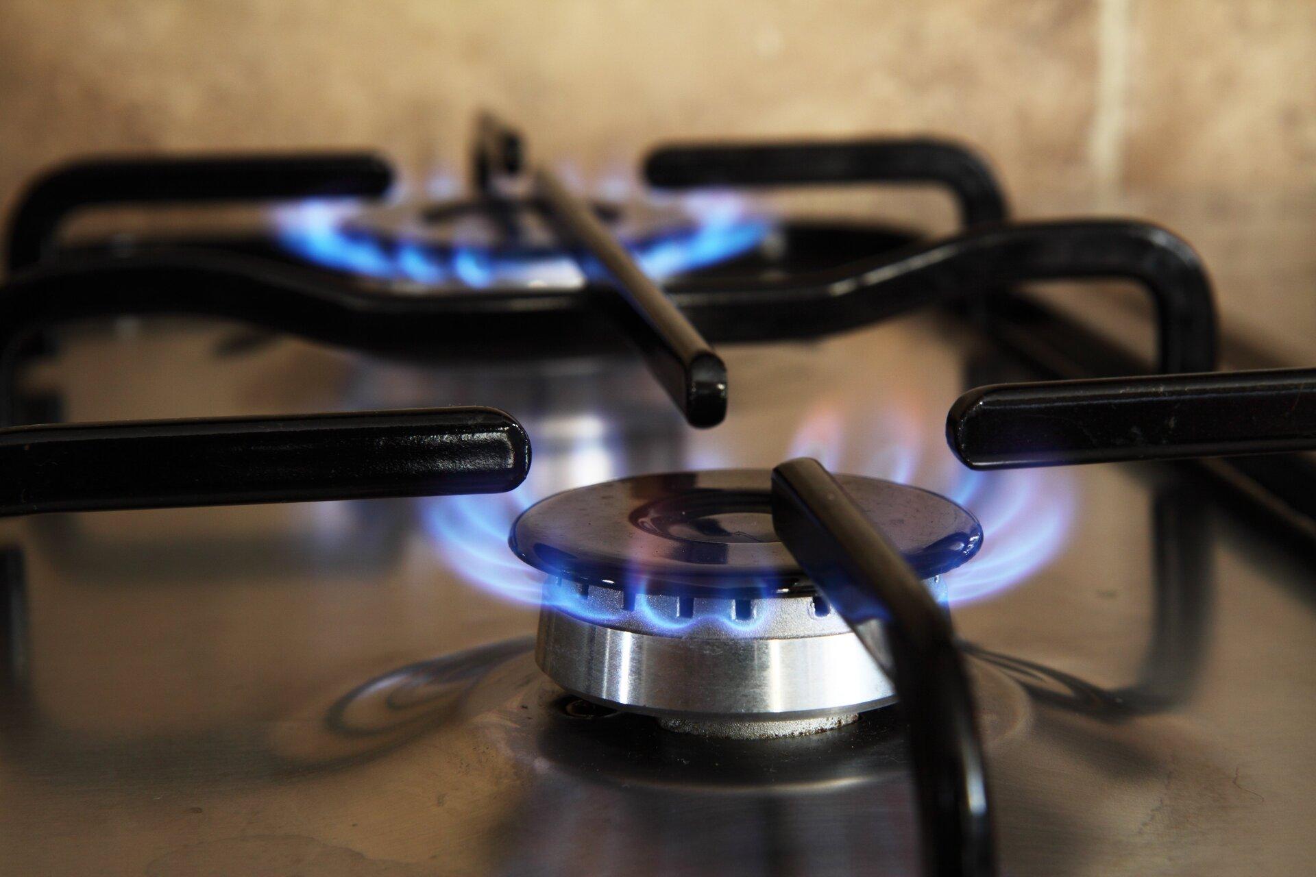 Zdjęcie przedstawia palące się niebieskim płomieniem dwa palniki domowej kuchenki gazowej. Zgodnie zopisem głównym składnikiem gazu ziemnego jest związek kowalencyjny onazwie metan.