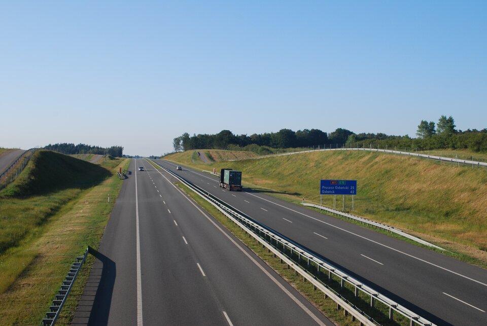 Na zdjęciu prosty odcinek autostrady, dwa pasy drogi ipobocze wkażdym kierunku, ogrodzona siatką.