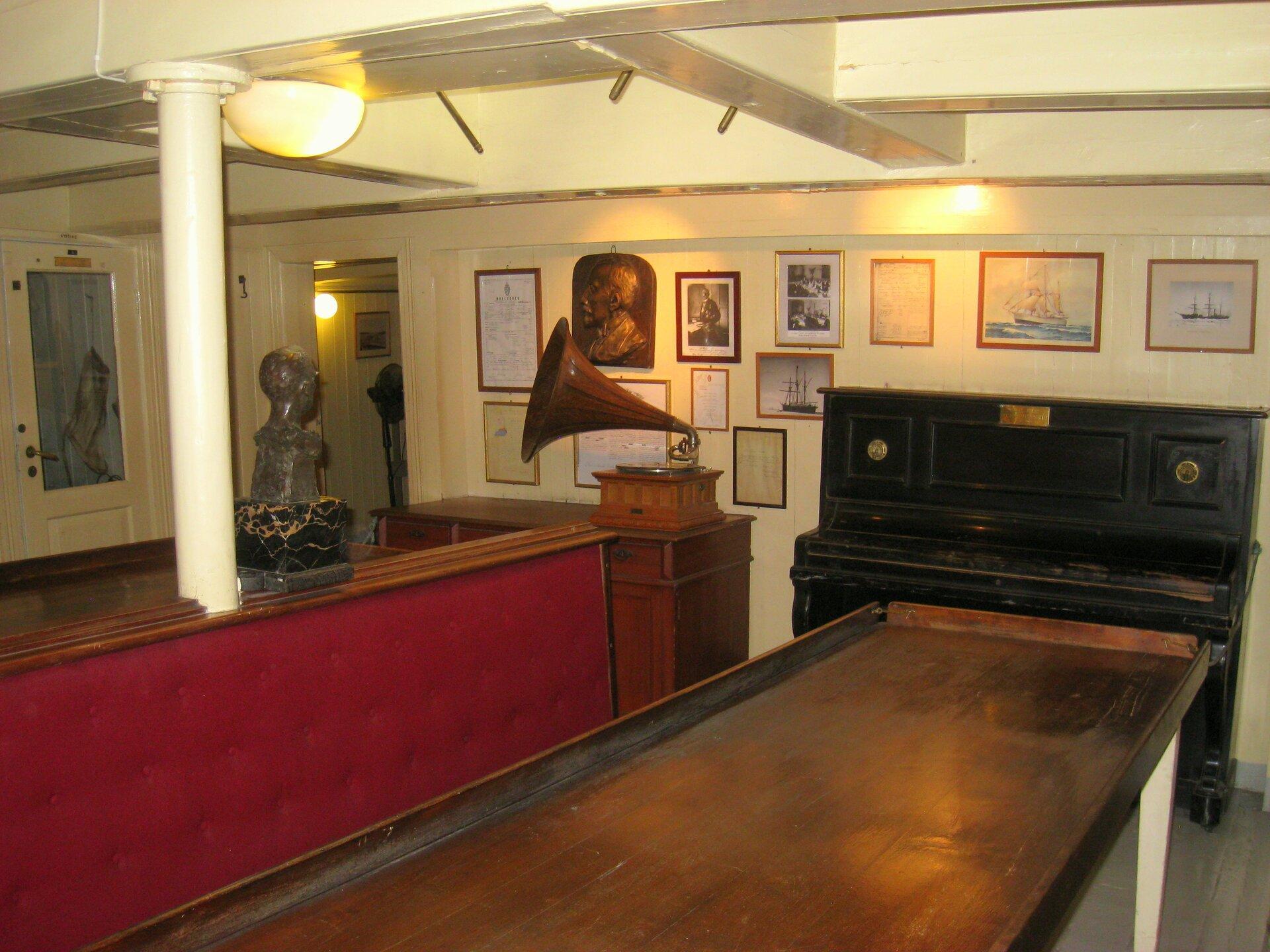 Na zdjęciu wnętrze, drewniane meble, pianino, gramofon, rzeźbione popiersie, na ścianach liczne obrazy.