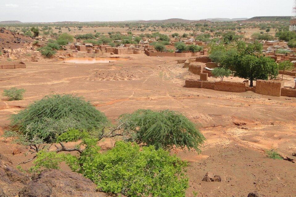 Na zdjęciu odkryta pustynna ziemia pozbawiona roślinności, dalej zabudowania otoczone murem, pojedyncze drzewa. Wtle góry.