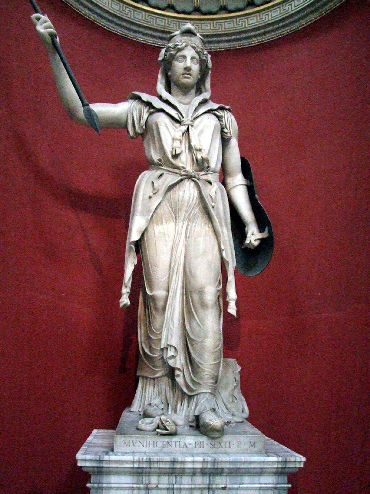 Rzeźba nieznanego autora przedstawia postać Junony -bogini rzymskiej, która została przedstawiona jako szczupła kobieta wśrednim wieku, ubrana wwelon zakrywający jej włosy, oraz długą szatę zakrywającą jej ciało. Junona jedną rękę ma uniesioną do góry itrzyma wniej włócznię, do drugiej ręki przymocowana została tarcza. Rzeźba została wykonana zjasnego kamienia, stoi na cokole, na którym widoczne są łacińskie inskrypcje. Figura Junony została sfotografowana na tle czerwonej ściany.