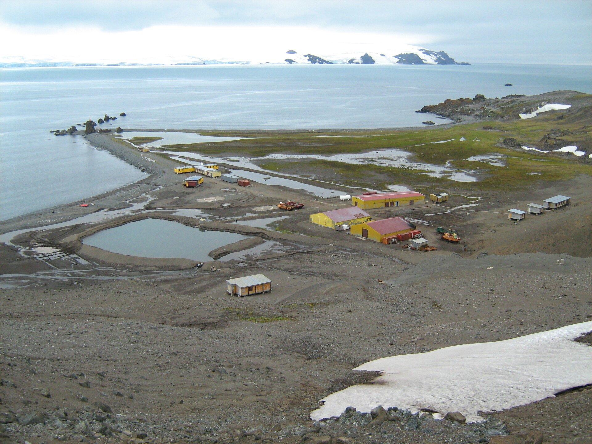 Fotografia wykonana zwysokości prezentuje Polską Stację Arktyczną im. Henryka Arctowskiego. Widoczny płaski teren nad morzem zniskimi prostokątnymi budynkami różnej wielkości oraz koloru żółtego ibiałego. Część trenu pokryte jest stojącą wodą ztopniejącego śniegu.