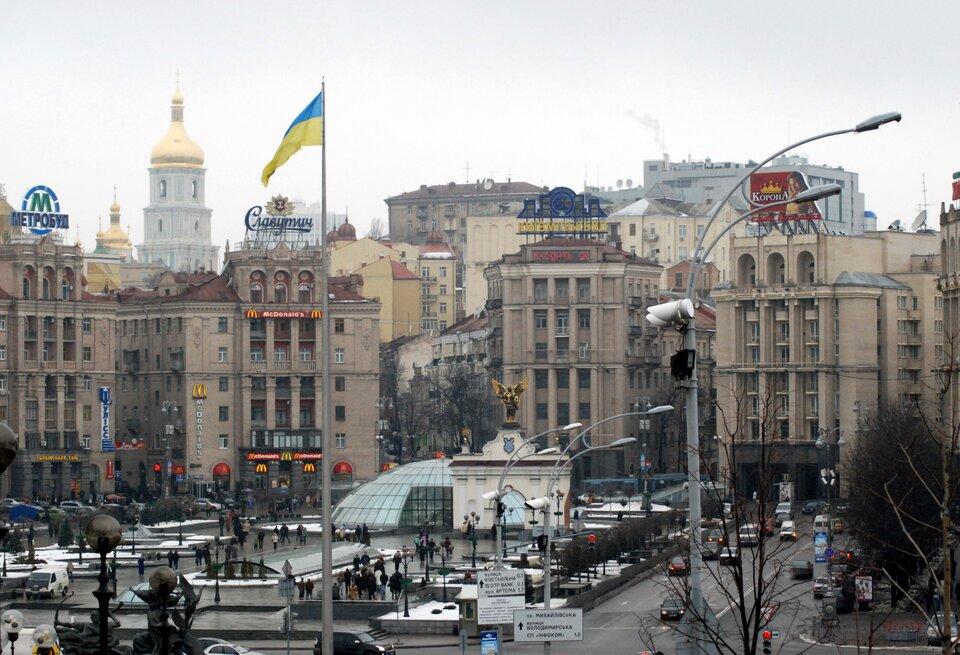 Widok na rozległy plac wwiekim mieście. Dokoła placu wysokie kamienice.