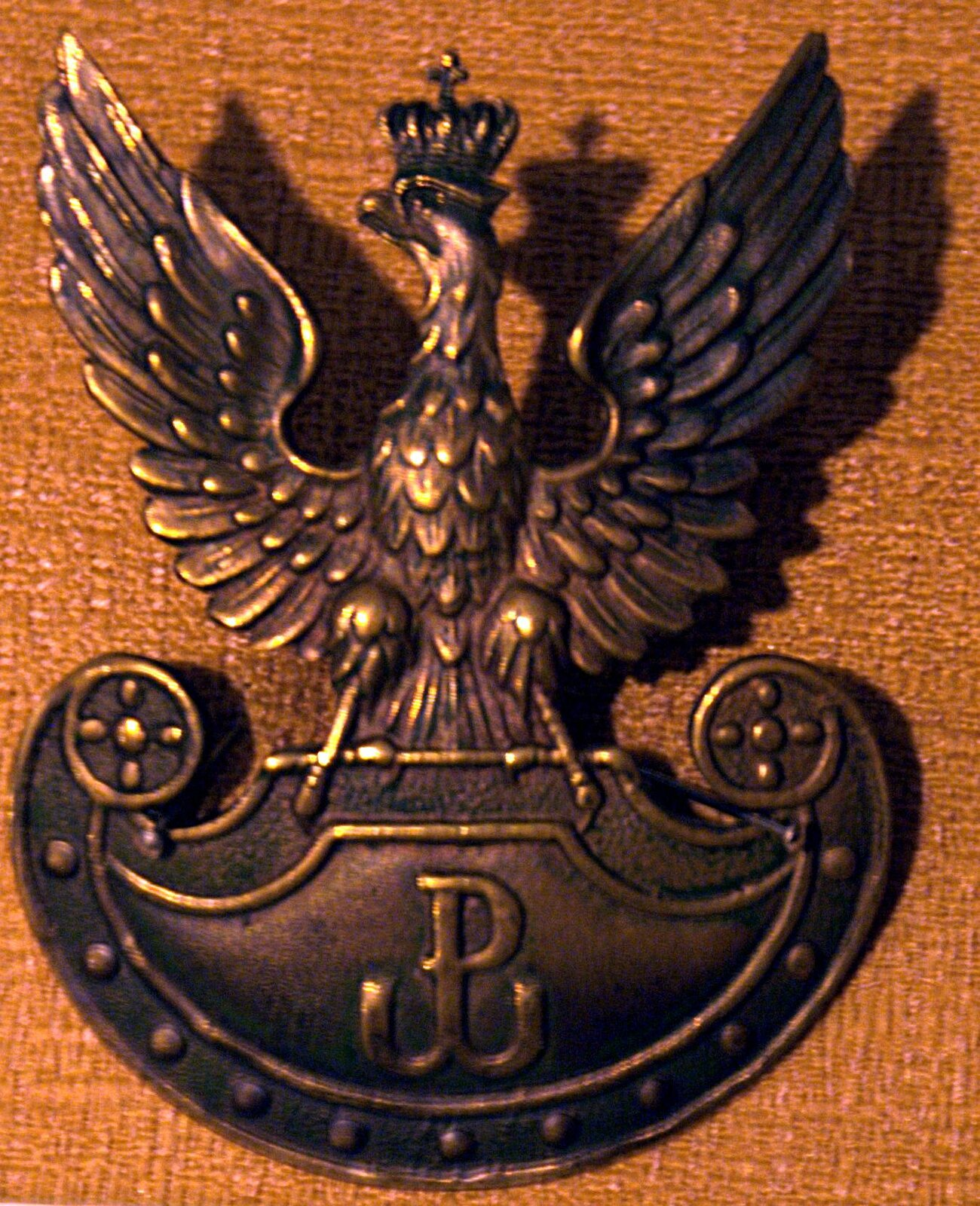 Mosiężny orzełek Armii Krajowej, bity wlatach 1942-45 Mosiężny orzełek Armii Krajowej, bity wlatach 1942-45 Źródło: Muzeum Hymnu Narodowego wBędominie, licencja: CC BY-ND 1.0.