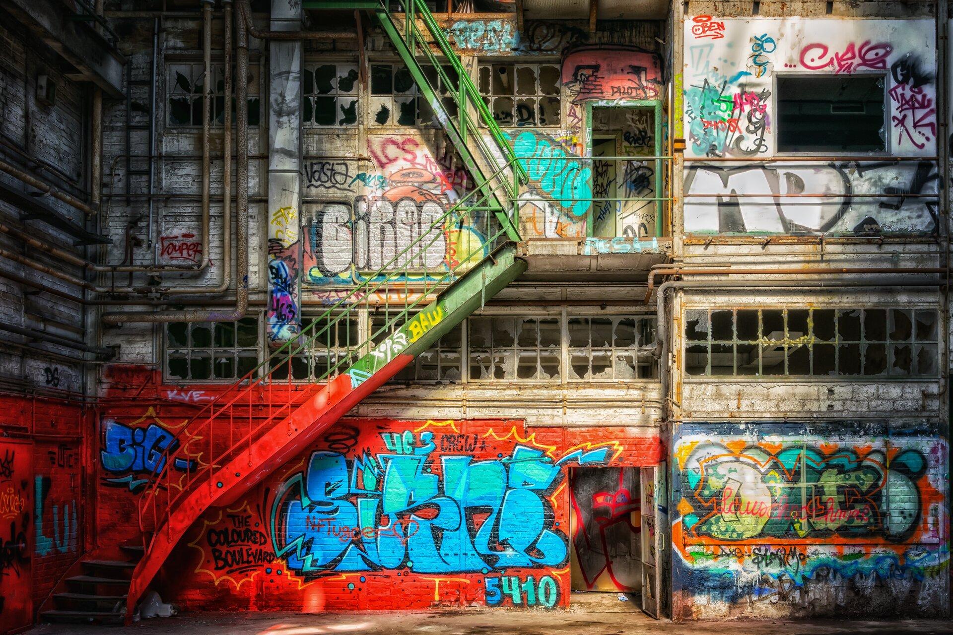 Ilustracja przedstawia zdjęcie, na którym cały budynek został zamalowany wielobarwnymi graffiti. Są to głównie duże napisy otoczone czarnymi konturami. Dodatkowo wprowadzono też krótkie hasła pisane sprayem, aczasem wypełniono jedną plamą barwną tło.