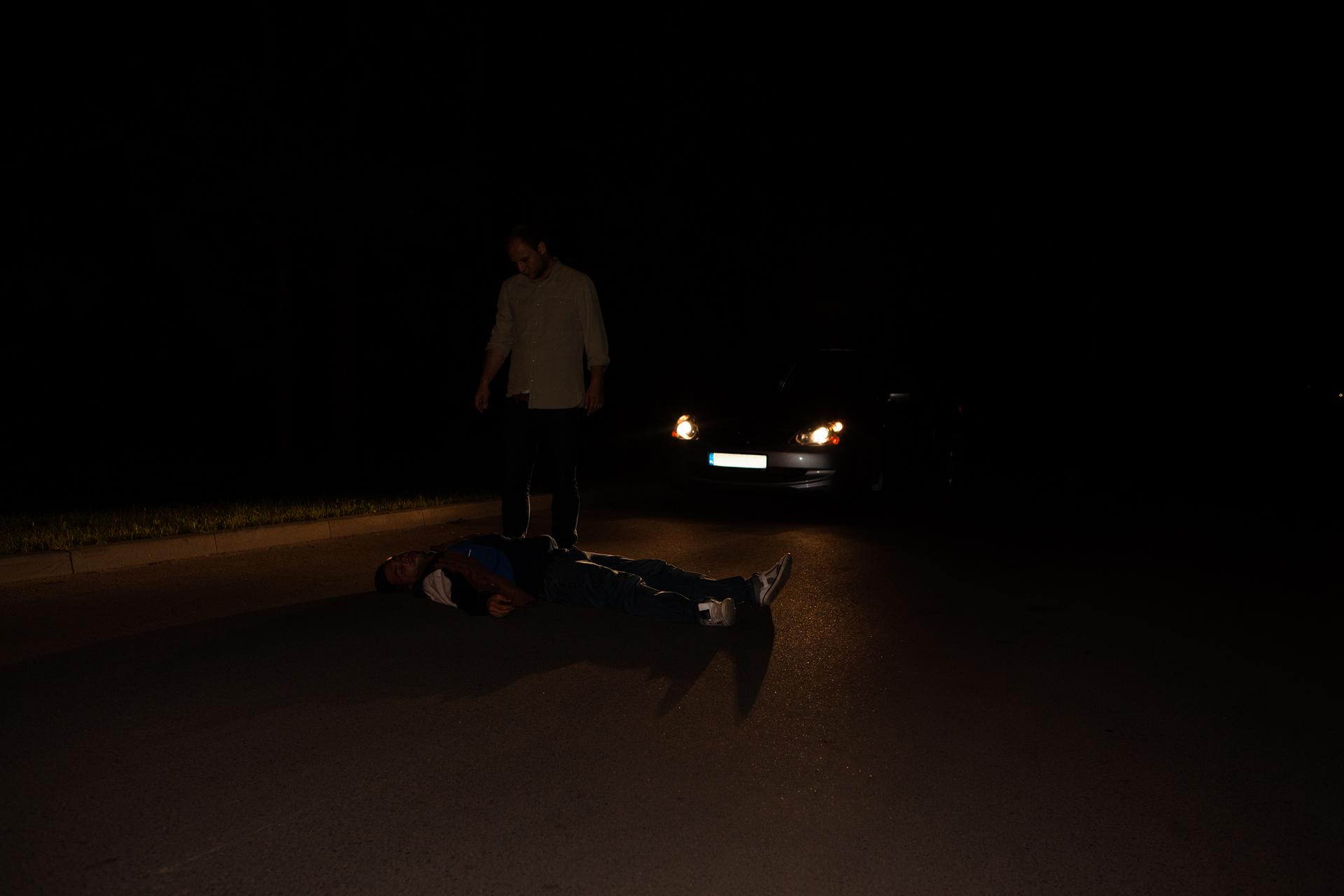 Dwa zdjęcia: dwa zdjęcia ułożone poziomo. Noc. Pierwsze zdjęcie po lewej stronie. Na jezdni leży nieprzytomna osoba. Leżąca osoba ubrana na czarno bez odblaskowych dodatków. Za leżącą osobą zaparkowany samochód zwłączonymi reflektorami. Reflektory skierowane na leżącą osobę. Kierowca bez kamizelki odblaskowej jest prawie niewidoczny na jezdni.
