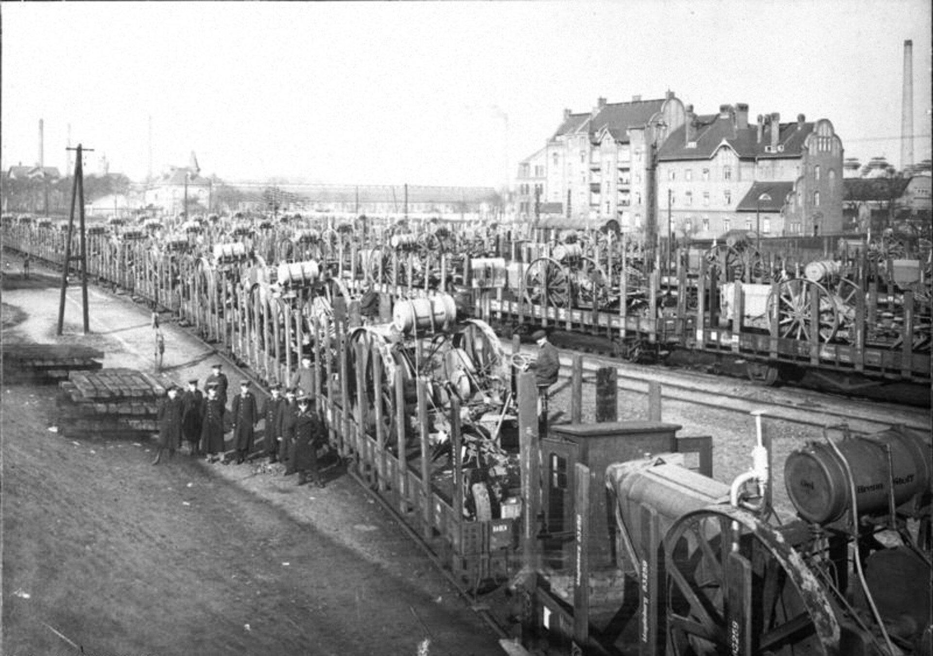 Fotografia czarno-biała przedstawiająca niemieckie reparacje. Na ilustracji widać dworzec kolejowy na którym stoją pociągi wyładowane samochodami. Pociągi zajmują trzy tory. Przed pierwszym pociągiem stoi garstka ludzi, którzy rozmawiają, ubrani są wwojskowe mundury.