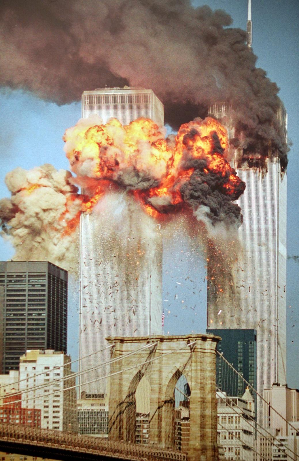Zdjęcie przedstawia moment zderzenia samolotów zwieżami WTC wNowym Jorku w2001 roku. Górna część pierwszej wieży otoczona jest kłębami czarnego dymu ipłomieniami ognia. Druga wieża, stojąca za pierwszą, jest zniszczona poniżej dachu. Górną część drugiej wieży zakrywa gęsty czarny dym unoszący się wlewą stronę. Wokół budynków spadają kawałki szkła ifasady.