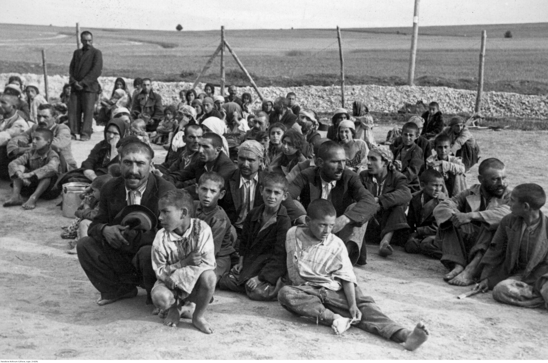 Stara fotografia. Na zdjęciu grupa Cyganów siedzących na ziemi, dorośli idzieci. Za nimi ogrodzenie. Jeden mężczyzna stoi przy ogrodzeniu.