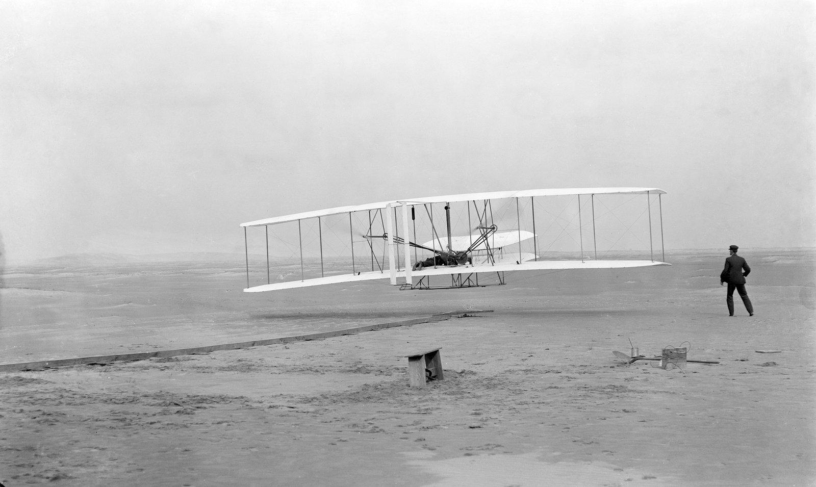 Pierwszy udany lot Wright Flyer Źródło: John T. Daniels, Pierwszy udany lot Wright Flyer, 1903, domena publiczna.