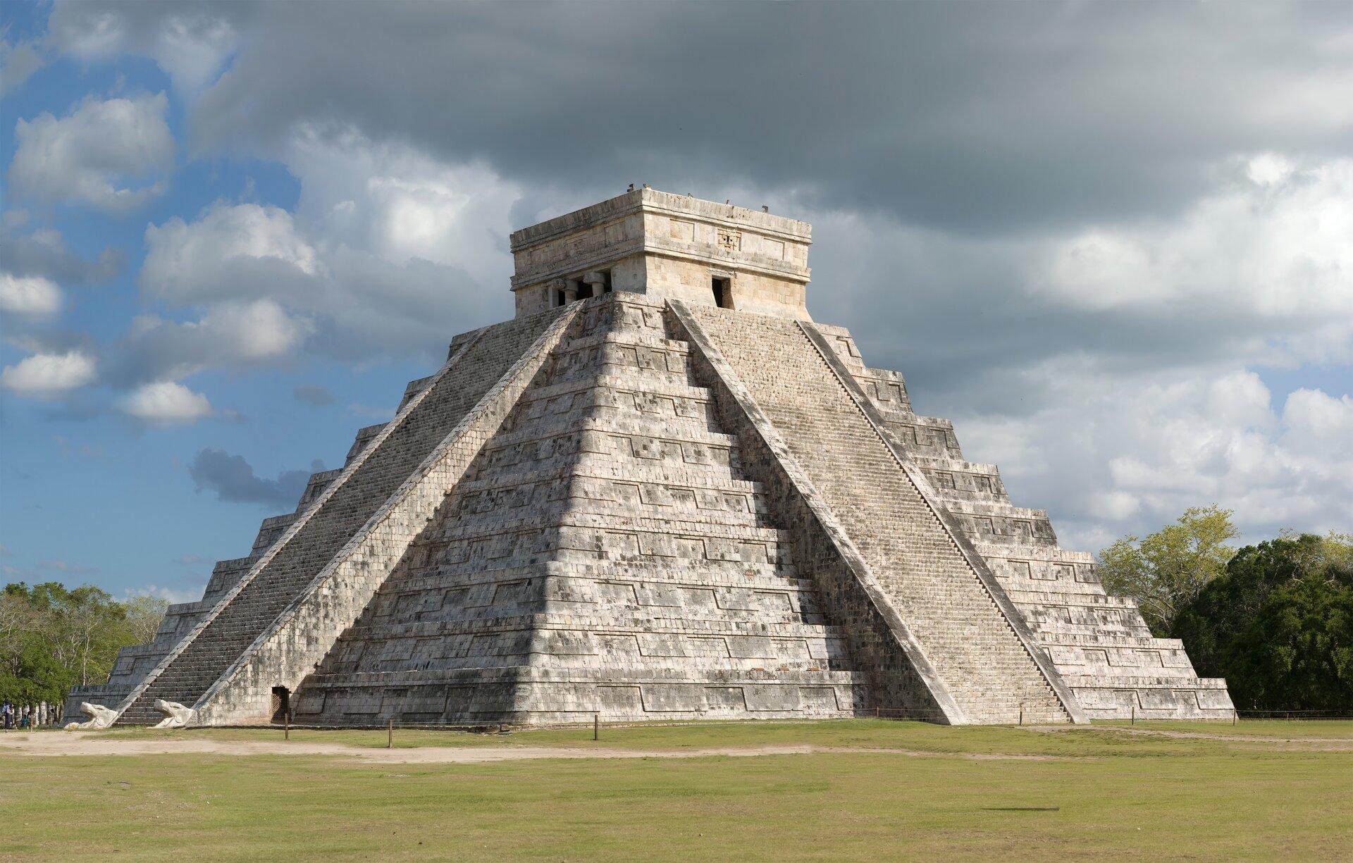 Na zdjęciu kamienna budowla wkształcie graniastosłupa okwadratowej podstawie, zwężającego schodkowo się ku górze. Upodstawy teren trawiasty.