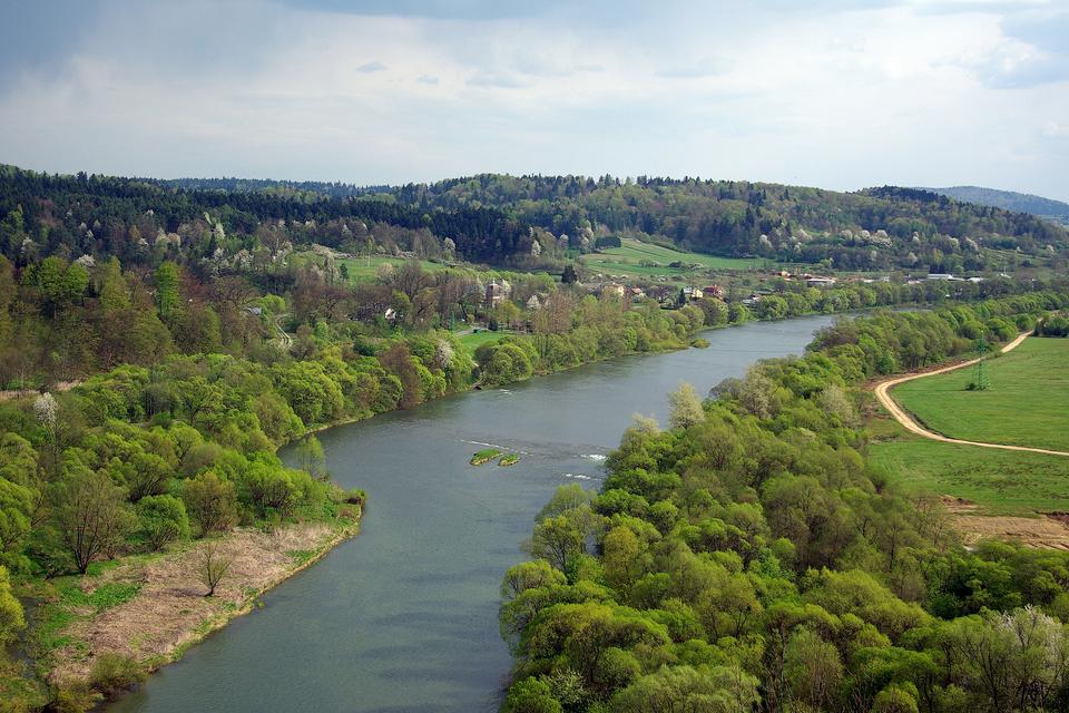 Fotografia przedstawia bieg środkowy rzeki - rzeka ma szerokie koryto przecinające teren pagórkowaty.