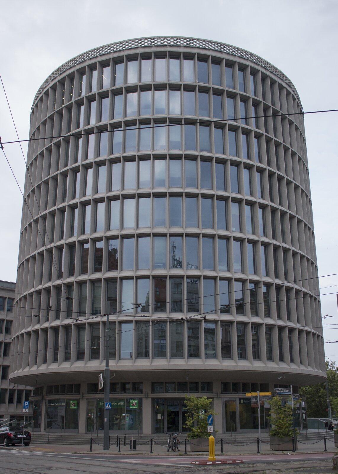 """Ilustracja przedstawia """"Okrąglak"""" wPoznaniu autorstwa architekta Marka Leykama. Zdjęcie ukazuje szary, dziewięciokondygnacyjny budynek wkształcie walca. Parterowa, najwyższa część ustawiona jest na schodkach ima najmniejszą średnicę. Nad nią wznoszą się pozostałe, szersze piętra ze składająca się zokien, poprzedzielanych szarymi elementami konstrukcji fasadą."""