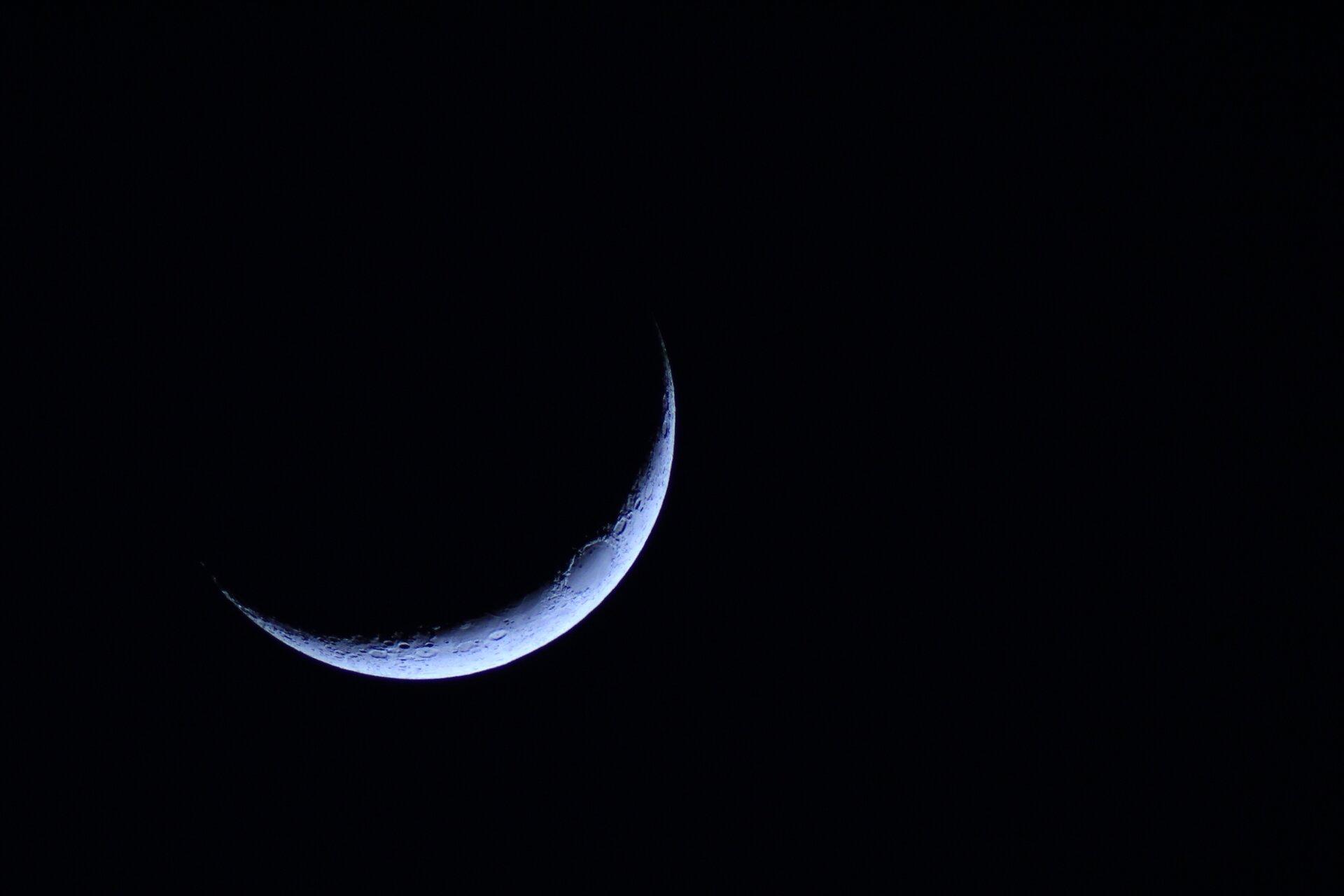 """Ilustracja przedstawia księżyc. Tło czarne. Księżyc srebrno-szary. Księżyc widoczny jako cienki """"rogalik""""."""