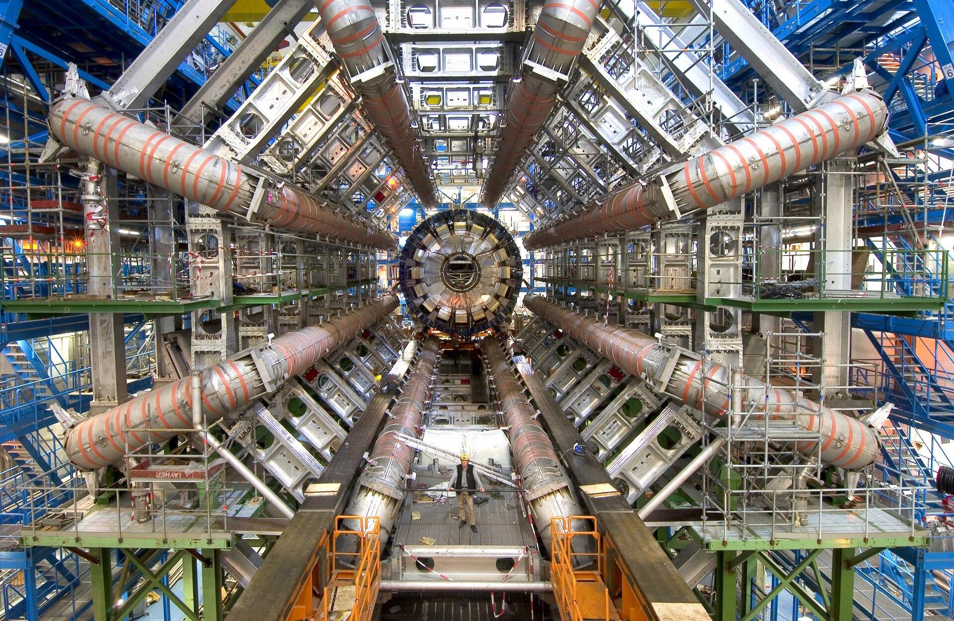 Zdjęcie przedstawia wnętrze ogromnego tunelu rozszerzającego się wpomieszczenie pełne skomplikowanych urządzeń. Uwagę zwraca przede wszystkim osiem koncentrycznie równomiernie ciągnących się wzdłuż tunelu rur oznaczonych czerwonymi pasami. Otaczające całą maszynerię rusztowania, platformy ischody oraz przede wszystkim znajdujący się na pierwszym planie człowiek wżółtym kasku stojący pomiędzy dwoma rurami, zktórych każda okazuje się mieć ponad metr średnicy doskonale pokazują skalę kolosalnych rozmiarów całego kompleksu, który jest tak naprawdę jednym urządzeniem.