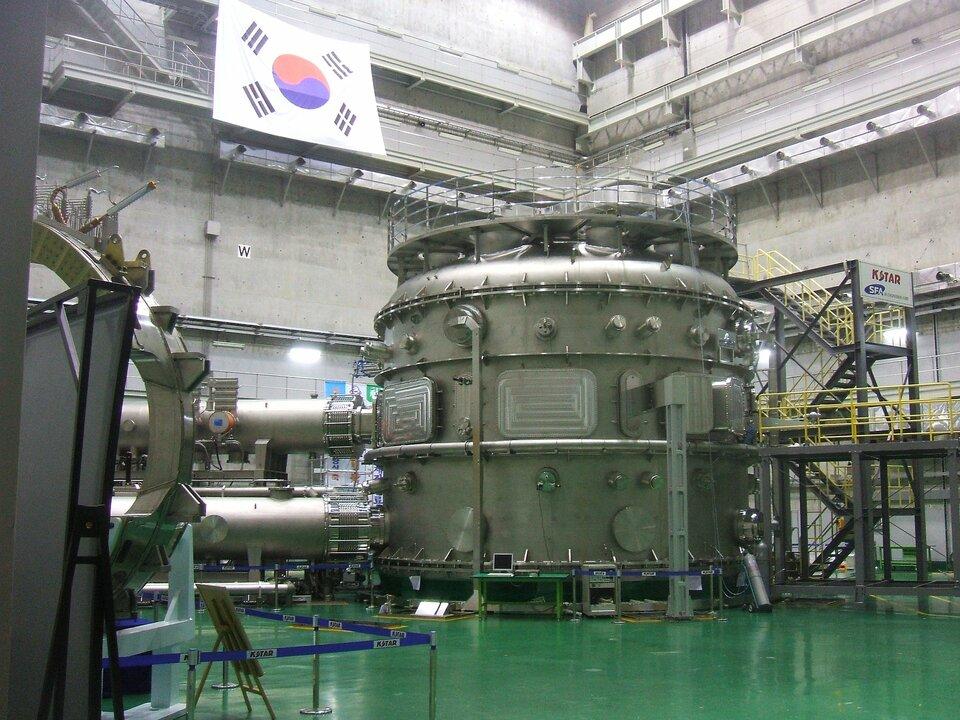 Zdjęcie przedstawia tokamak wKorei Południowej stojący wdużym pomieszczeniu fabrycznym ozielonej podłodze. Wysoko na platformie obserwacyjnej wisi flaga Korei. Sam tokamak ma postać dużego, beczkowatego urządzenia, od którego zlewej strony odchodzi system rur. Rusztowania wokół pozwalają ocenić wysokość maszyny na co najmniej osiem metrów.