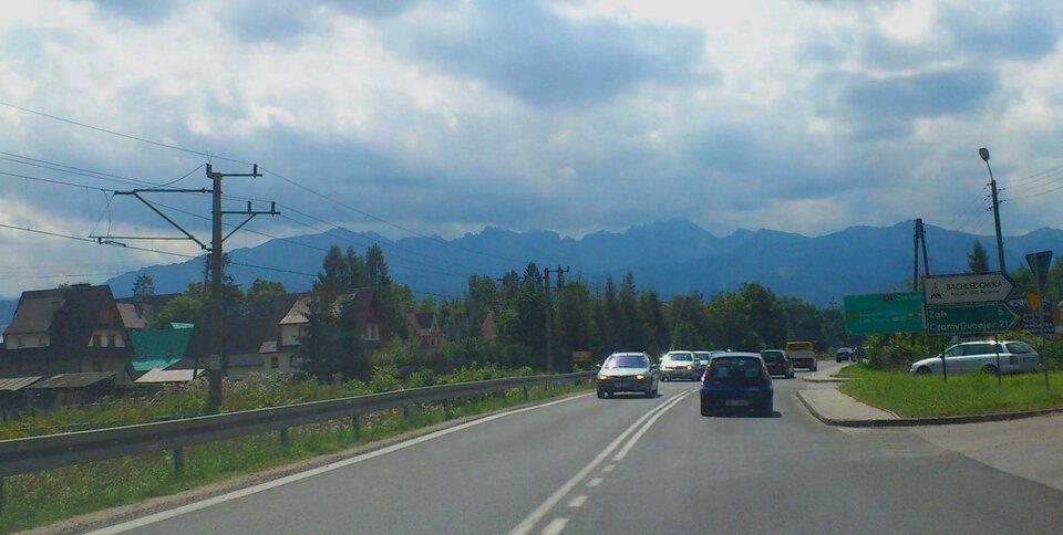 Na zdjęciu droga asfaltowa, sznur samochodów, wzdłuż drogi linia kolejowa, wtle góry.