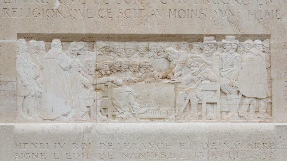 """Reliefna pomniku reformacji wGenewie przedstawiający podpisanie edyktu nantejskiego przez Henryka IV w1598 r. Więcej osamym pomniku - por. informacje zlekcji 88.Udołu napis """"HENRI IV ROI DE FRANCE ET DE NAVARRE SIGNE L'EDIT DE NANTES LE 13 AVRIL 1598"""" (Henryk IV król Francji iNawarry podpisuje edykt Nantejski 13 kwietnia 1598). Reliefna pomniku reformacji wGenewie przedstawiający podpisanie edyktu nantejskiego przez Henryka IV w1598 r. Więcej osamym pomniku - por. informacje zlekcji 88.Udołu napis """"HENRI IV ROI DE FRANCE ET DE NAVARRE SIGNE L'EDIT DE NANTES LE 13 AVRIL 1598"""" (Henryk IV król Francji iNawarry podpisuje edykt Nantejski 13 kwietnia 1598). Źródło: Clément Bucco-Lechat, Wikimedia Commons, licencja: CC BY-SA 3.0."""