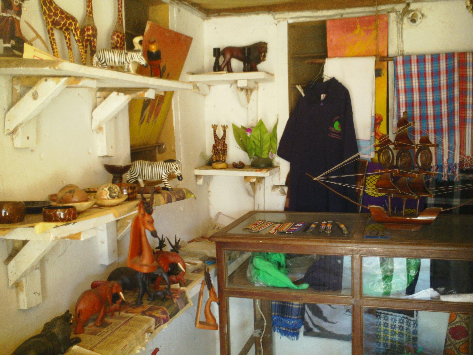 Na zdjęciu pomieszczenie zladą. Na ścianach półki. Na ladzie ipółkach ozdoby, figurki żyraf ilwa, model statku.