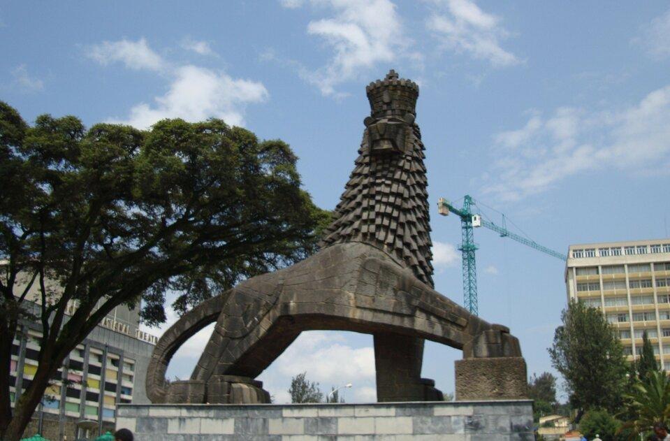 Na zdjęciu pomnika lwa, wtle wysokie budynki.