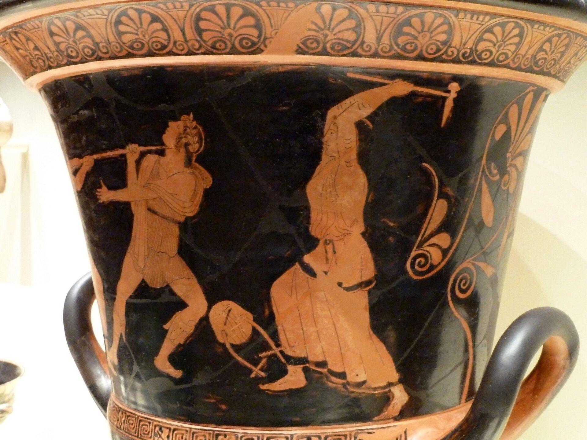 Na ilustracji przedstawiono fragment czerwonofigurowej wazy greckiej. Tematem malowidła jest śmierć Orfeusza zręki rozszalałej bachantki. Na czarnym tle wazy widnieje postać kobiety wjasnoczerwonej długiej szacie. Wuniesionych rękach trzyma narzędzie zbliżone wyglądem do młota, które kieruje wstronę Orfeusza. Pieśniarz ma odwróconą głowę. Pomiędzy walczącymi leży. Kompozycję zwieńczają motywy dekoracyjne ugóry iudołu wazy.